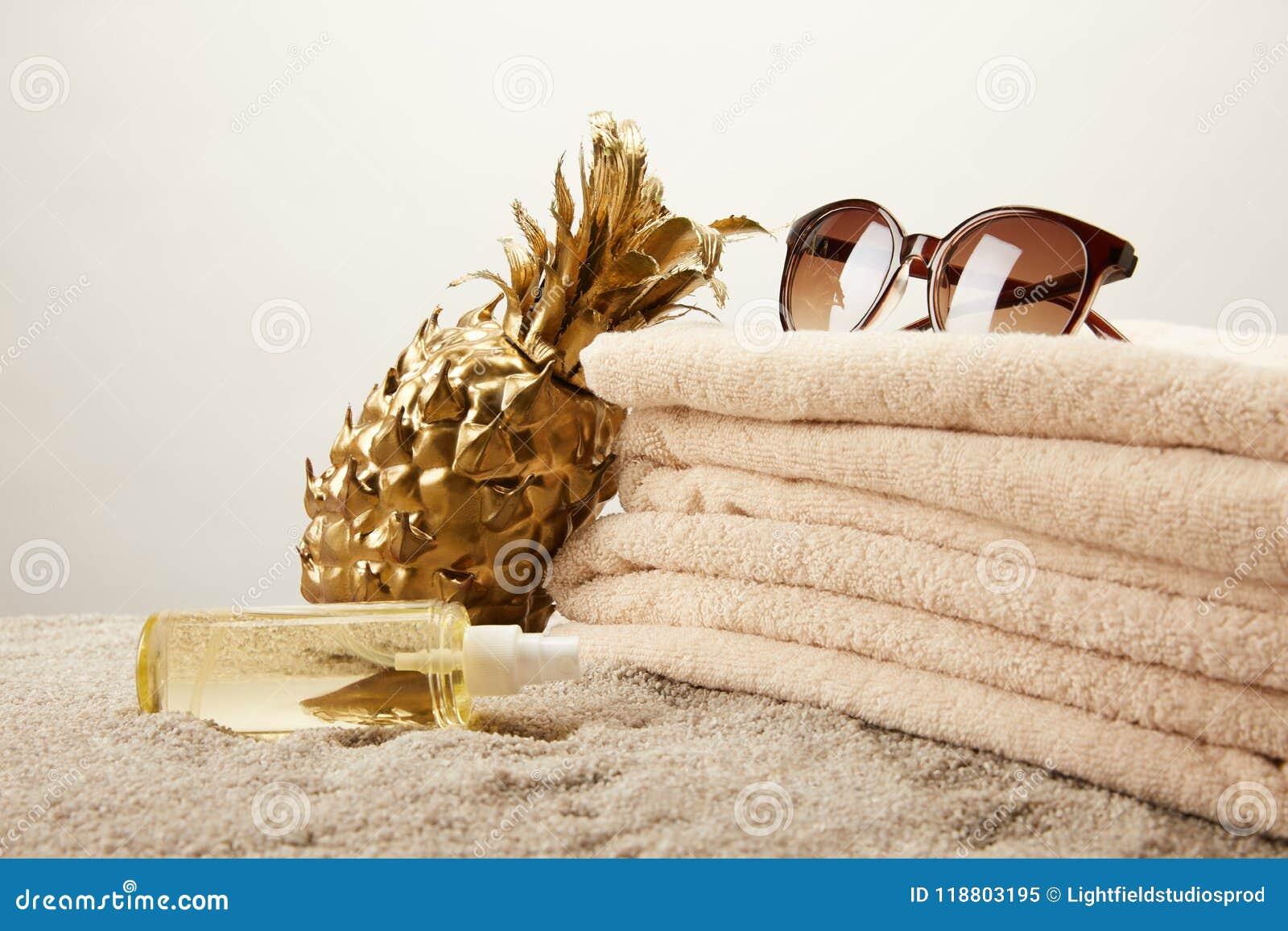Ciérrese encima de la vista de la pila de toallas, de gafas de sol, de aceite que broncea y de piña decorativa de oro en la arena