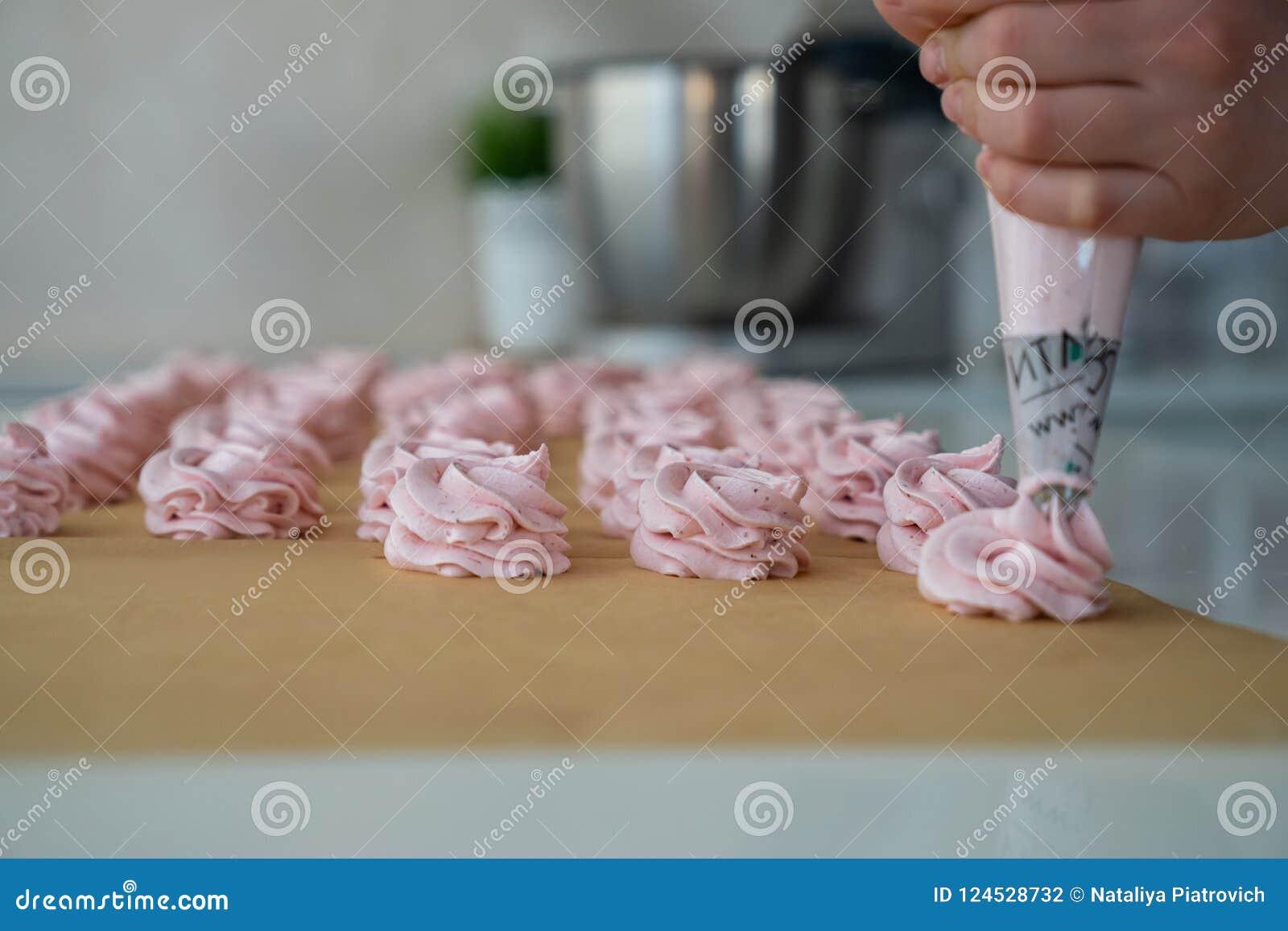 Ciérrese encima de las manos del cocinero con crema del bolso de la confitería al papel de pergamino en la cocina de la tienda de