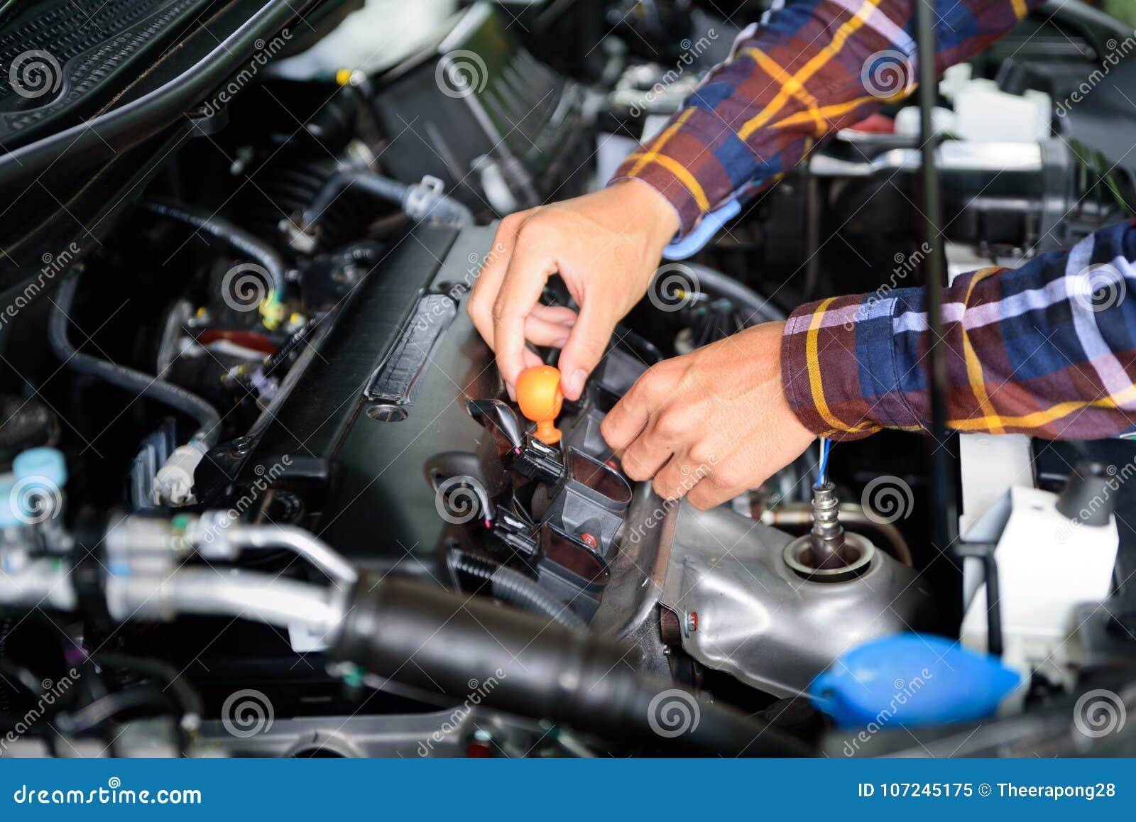 Ciérrese encima de las manos que comprueban el nivel de aceite de lubricante de motor de coche de profundo-s