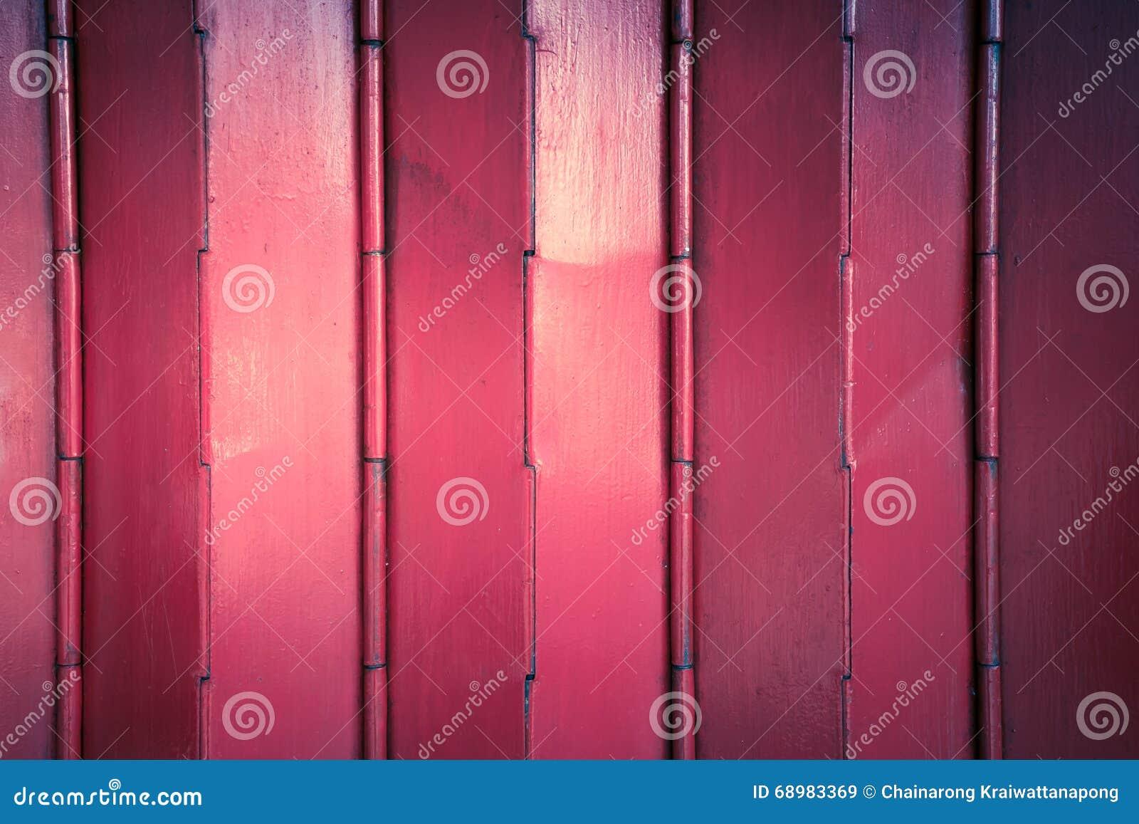 Ciérrese encima de las puertas del hierro labrado del color rojo