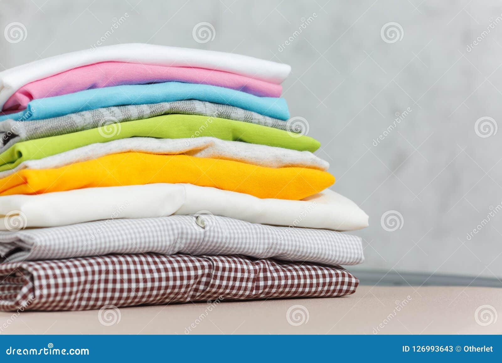 Ciérrese encima de lavadero lavado ropa colorida del hierro de vapor en el fondo blanco housekeeping Copie el anuncio del espacio
