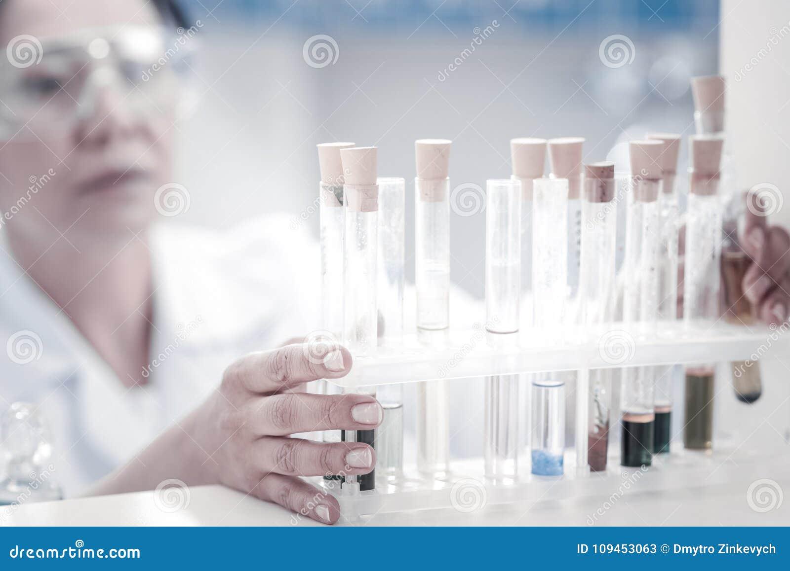 Ciérrese encima de mirada en el investigador de sexo femenino que toma el tubo de ensayo con el líquido