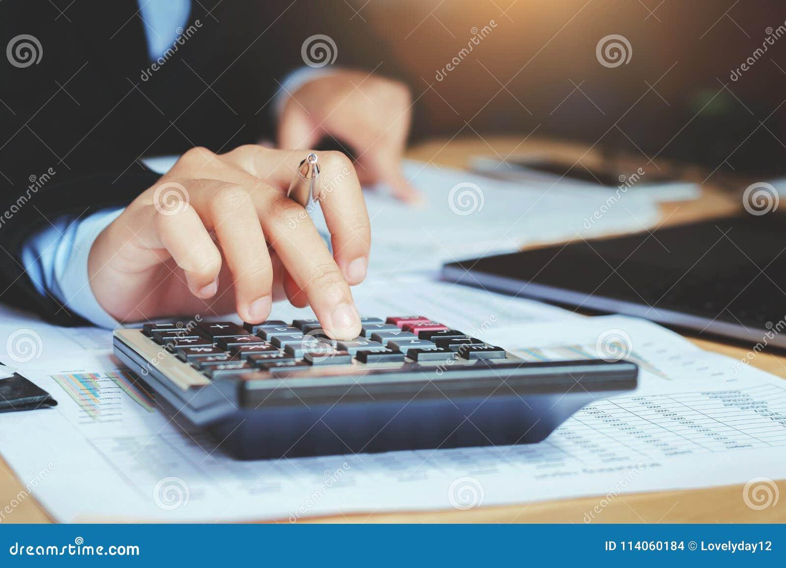 Ciérrese encima del contable de la mano que usa la calculadora con el ordenador portátil concepto s