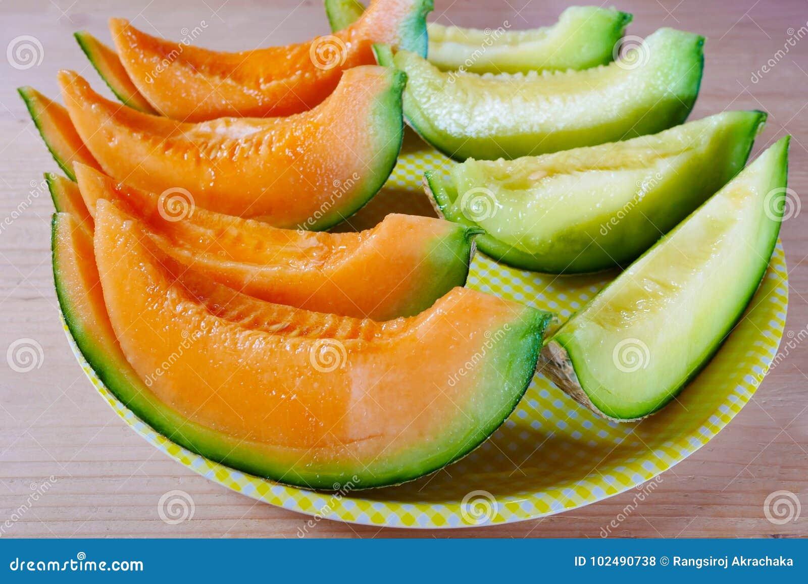 Ciérrese encima del melón cortado fresco con la placa en fondo de madera en la granja del melón en Furano, Hokkaido, Japón