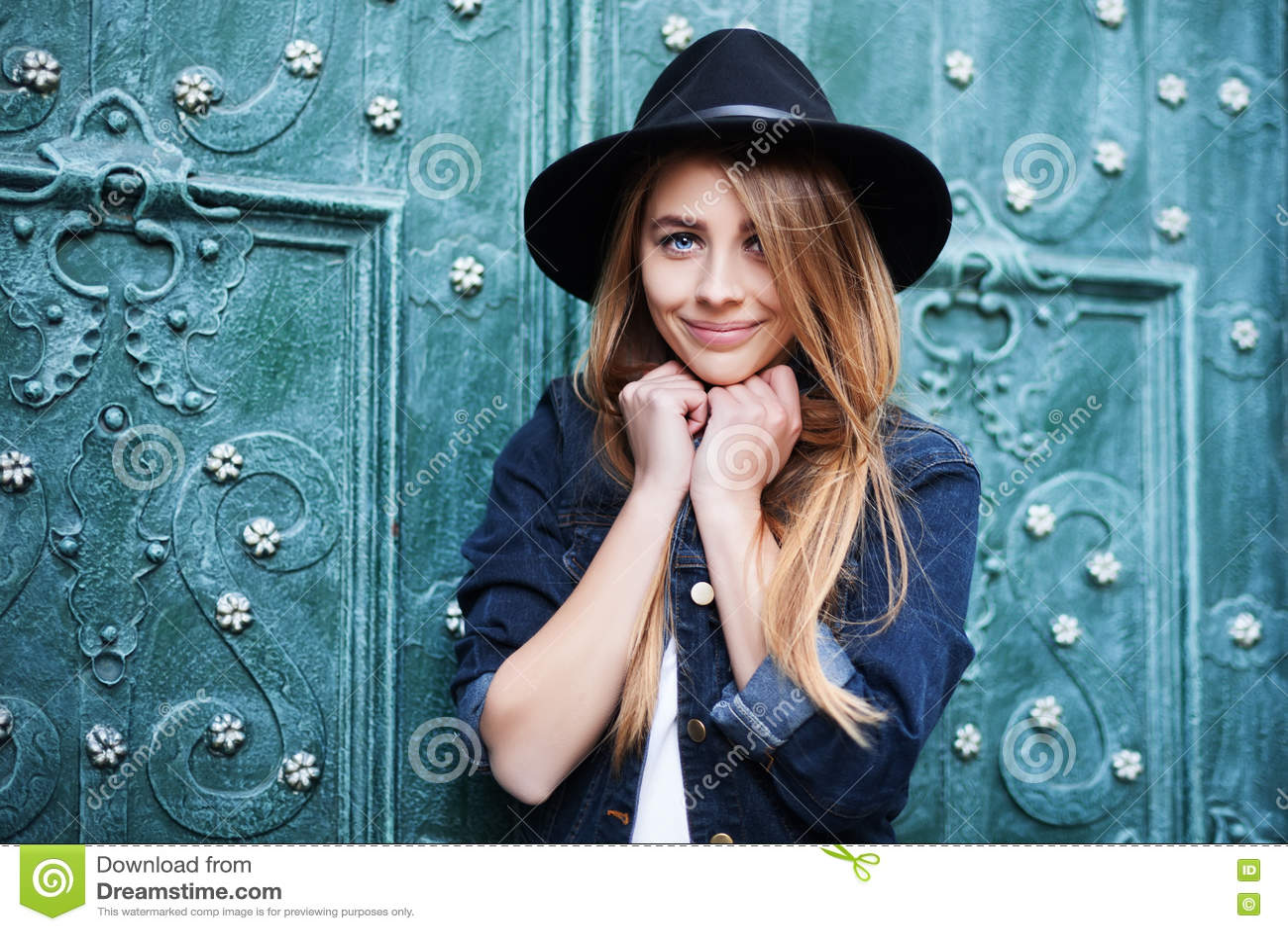 Ciérrese encima del retrato de la calle de la señora feliz sonriente de los jóvenes lindos que lleva el sombrero de ala ancha ele