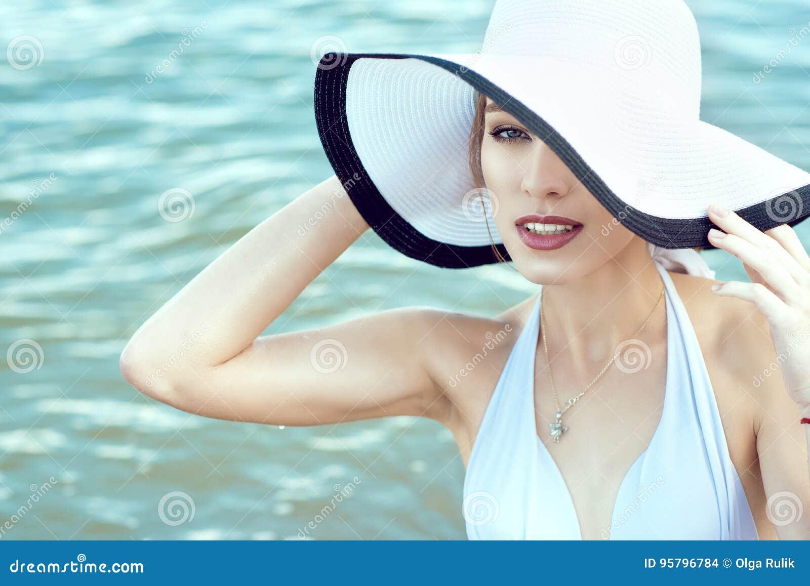Ciérrese encima del retrato de la señora atractiva elegante magnífica que oculta la mitad de su cara detrás del sombrero ancho de
