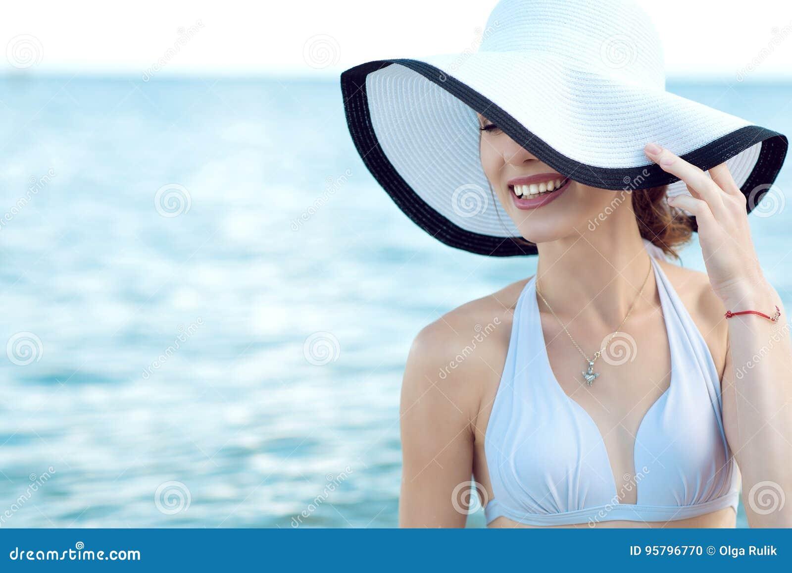 Ciérrese encima del retrato de la señora sonriente atractiva magnífica que oculta la mitad de su cara detrás del sombrero ancho d