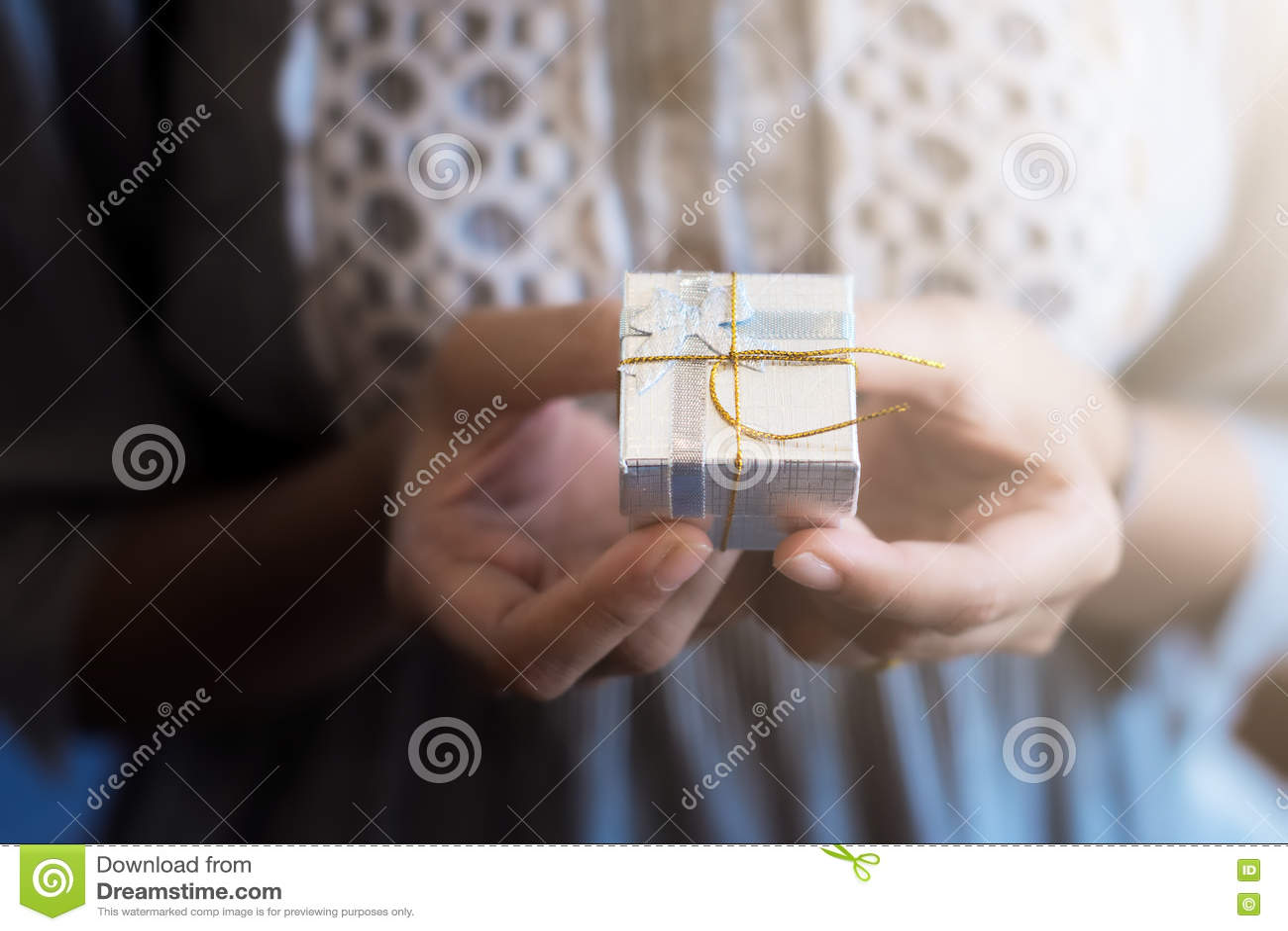 Ciérrese encima del tiro de las manos femeninas que sostienen un pequeño regalo