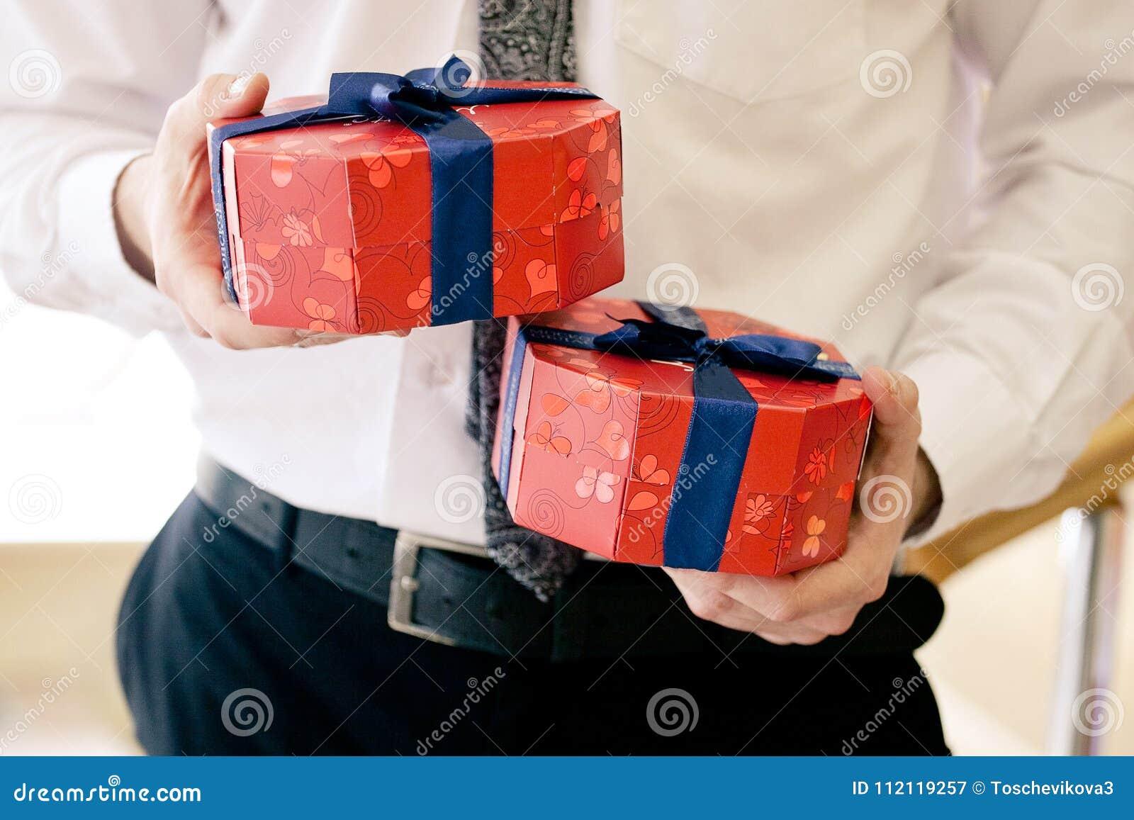 Ciérrese encima del tiro de las manos del hombre de negocios que sostienen las cajas de regalo brillantes envueltas con la cinta