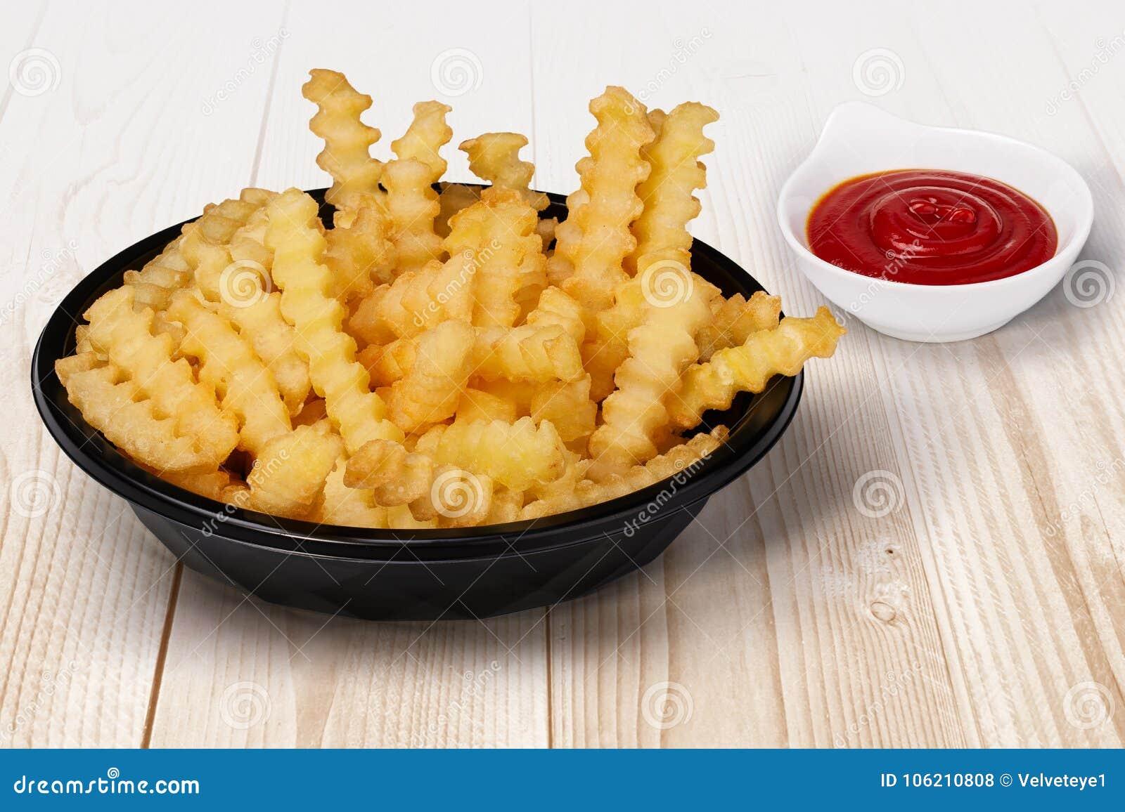 Ciérrese encima del tiro de las patatas fritas del corte de la arruga en la salsa de tomate negra del cuenco y de la salsa de tom