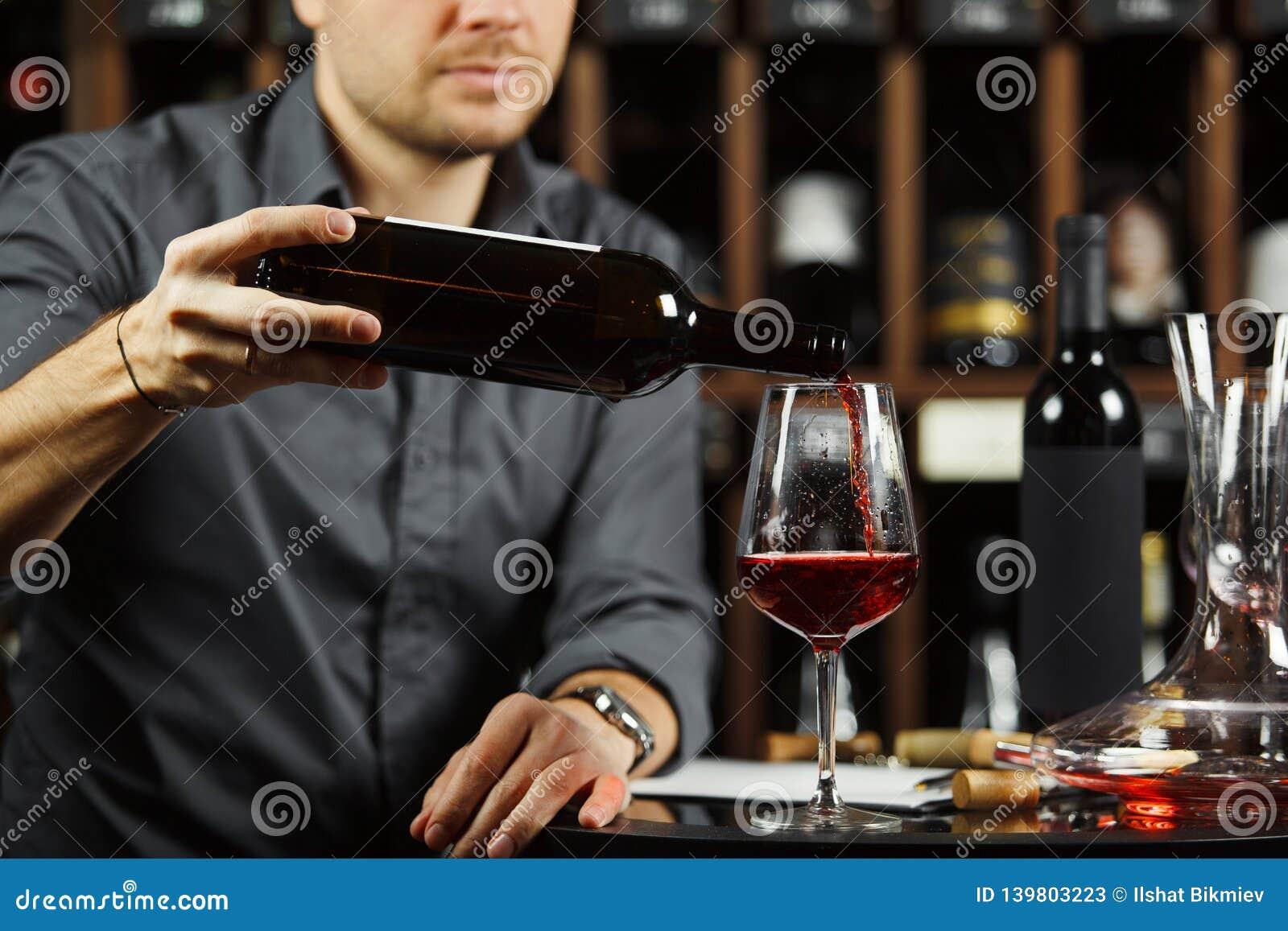 Ciérrese encima del tiro del sommelier que vierte el vino rojo de la botella en vidrio