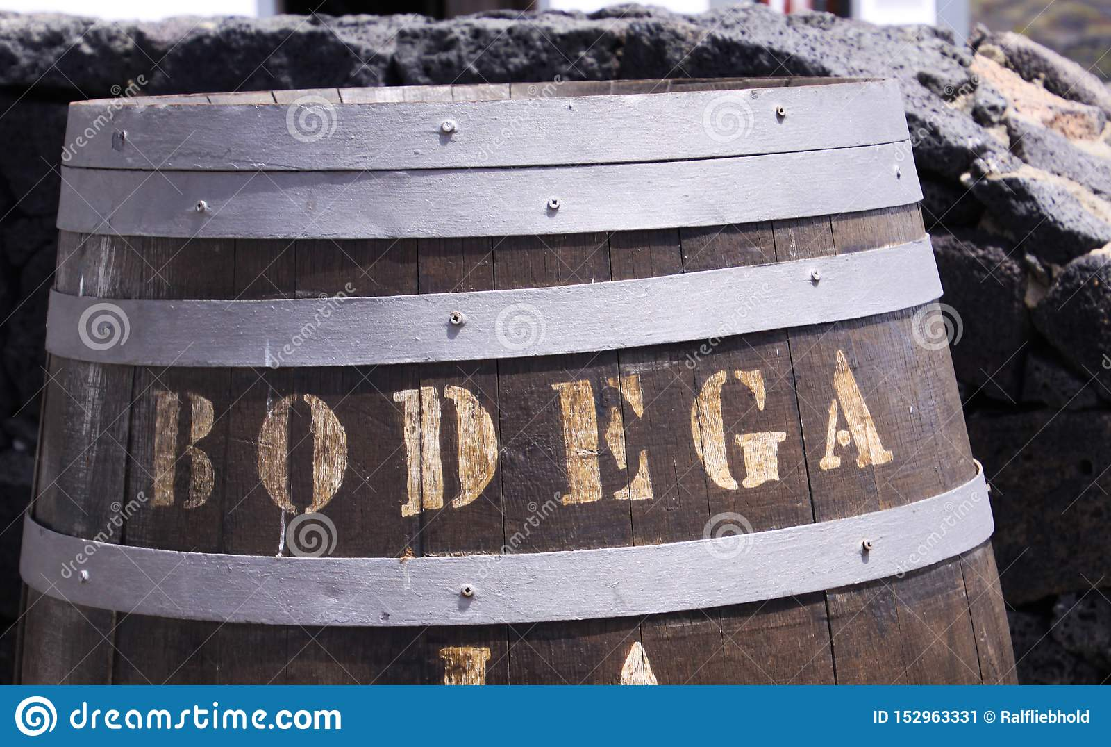 Ciérrese para arriba de barril de vino de madera con el Bodega del texto delante de la pared de piedra natural - Lanzarote