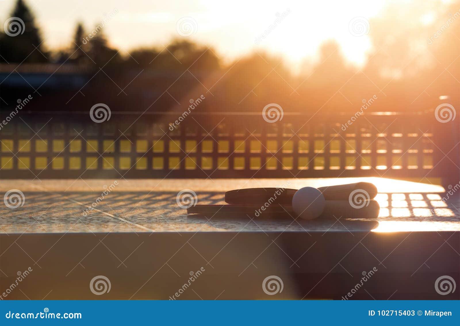 Ciérrese para arriba de bola de ping-pong con las estafas de tenis en la tabla de piedra en luces soleadas, equipo del tenis para
