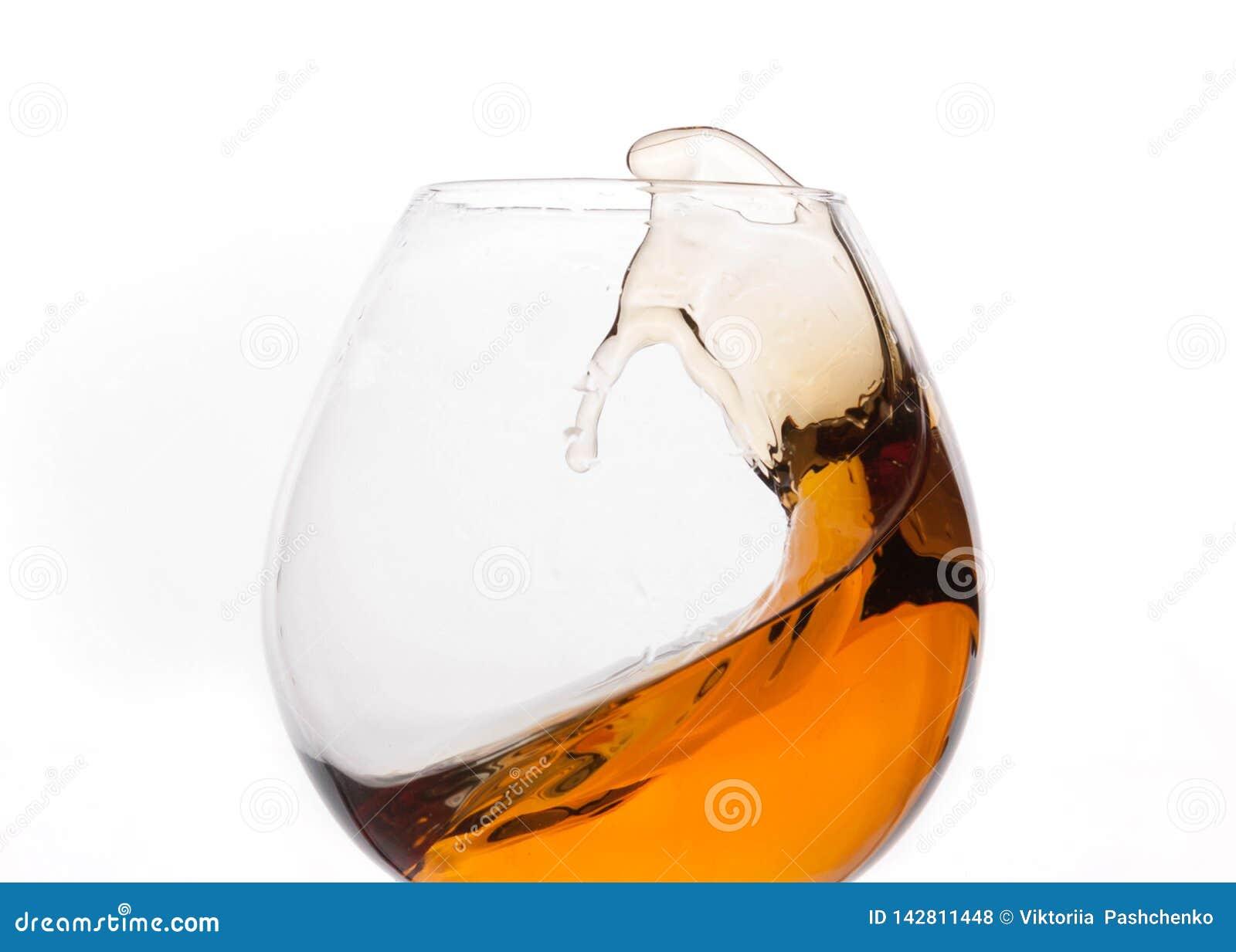 Ciérrese para arriba de chapoteo del whisky marrón en vidrio transparente