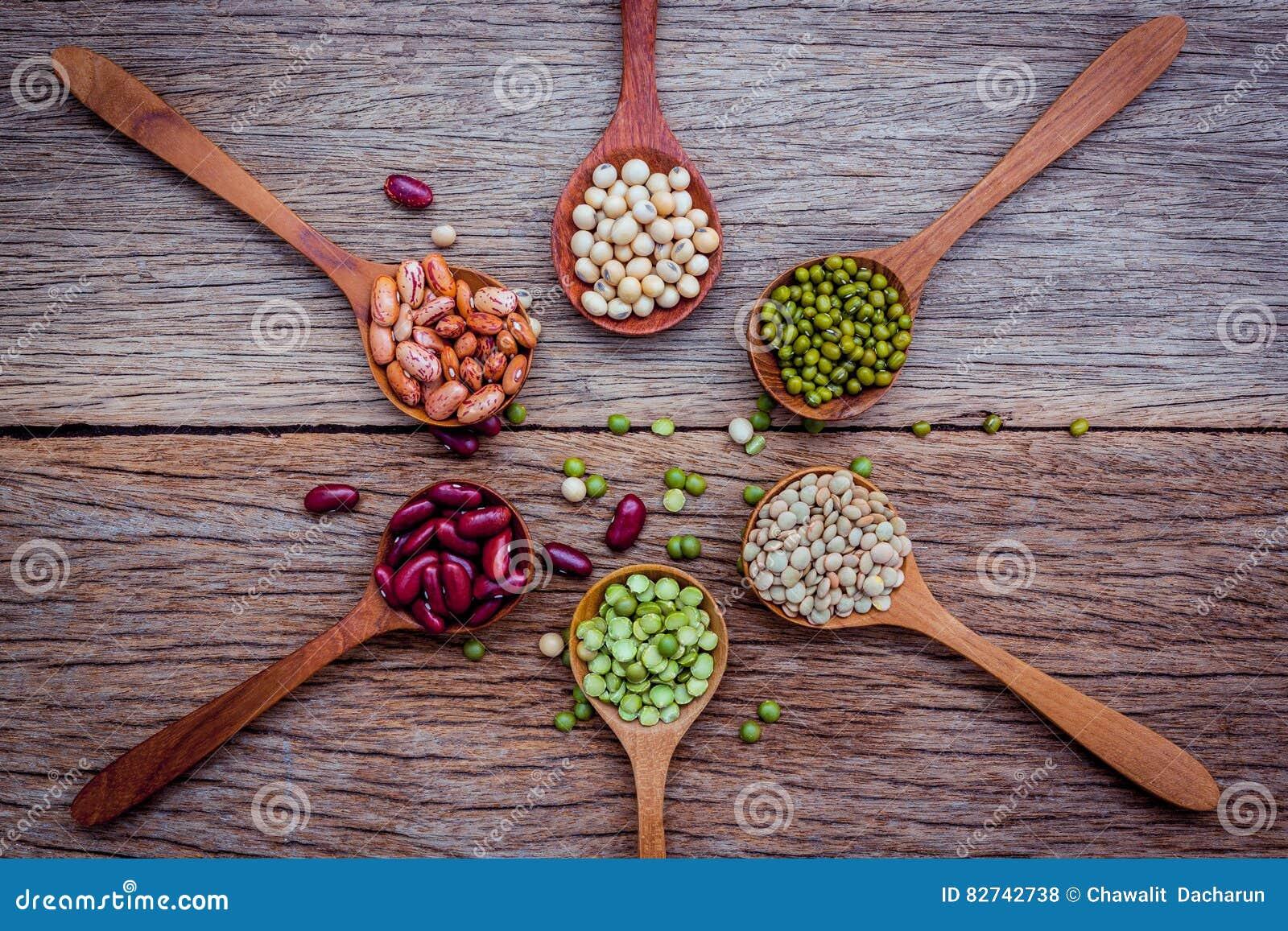 Ciérrese para arriba de diversas habas en las cucharas de madera puestas en fondo de madera
