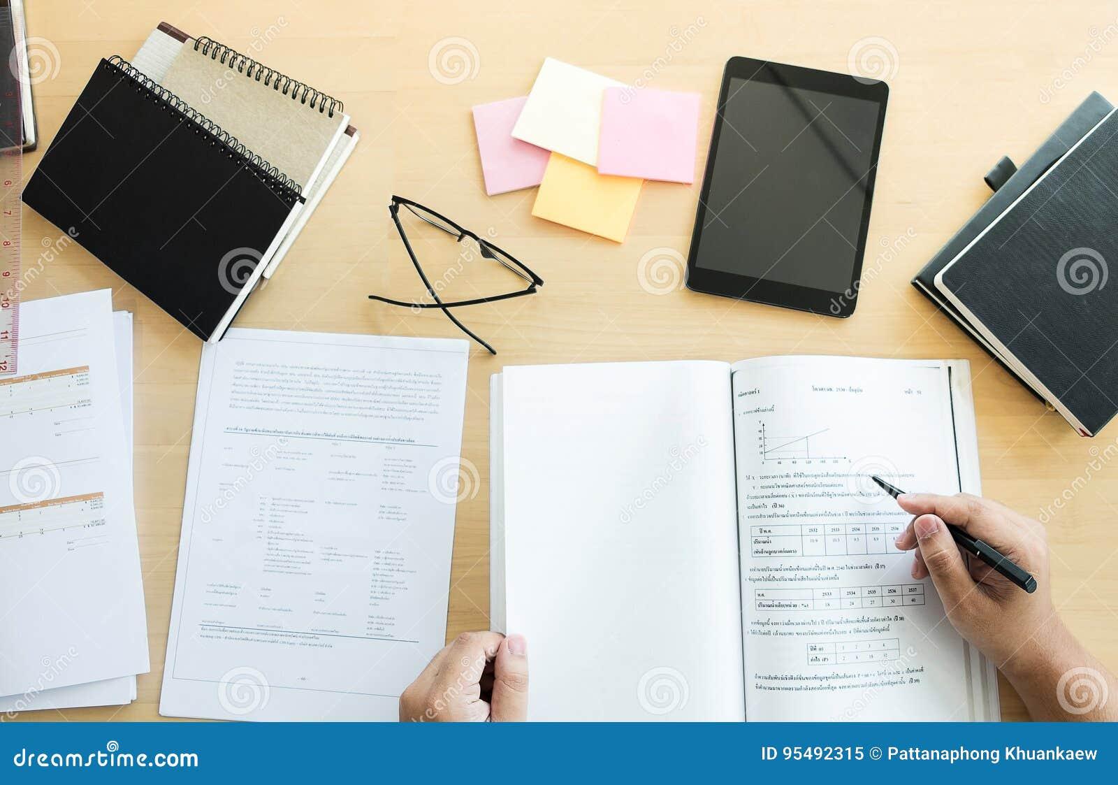 Ciérrese para arriba de estudiar las manos del estudiante que escriben en libro durante lectur