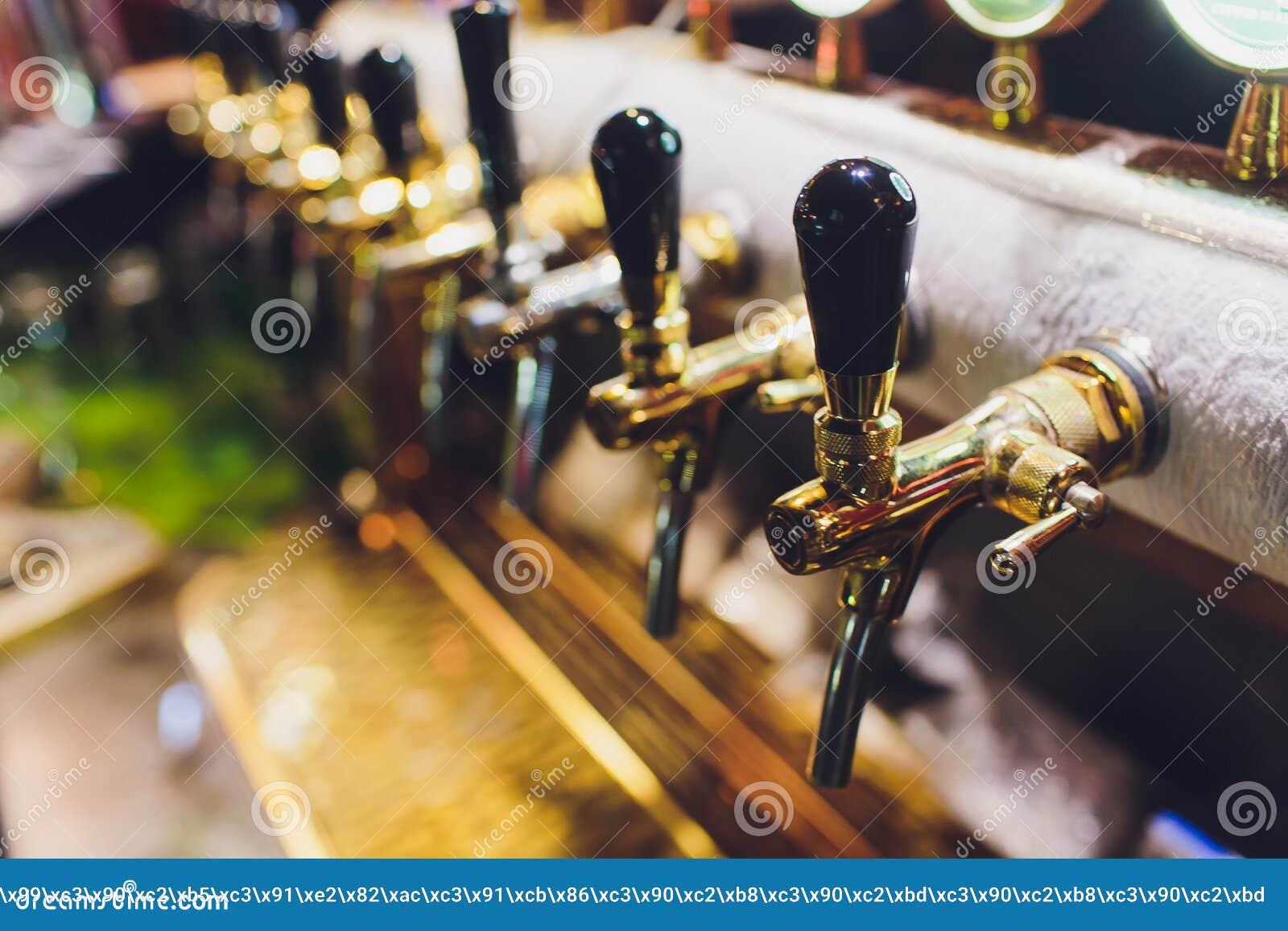 Ciérrese para arriba de golpecitos de la cerveza en fila Equipo metálico para las barras y los mini brewerys Concepto de equipo m