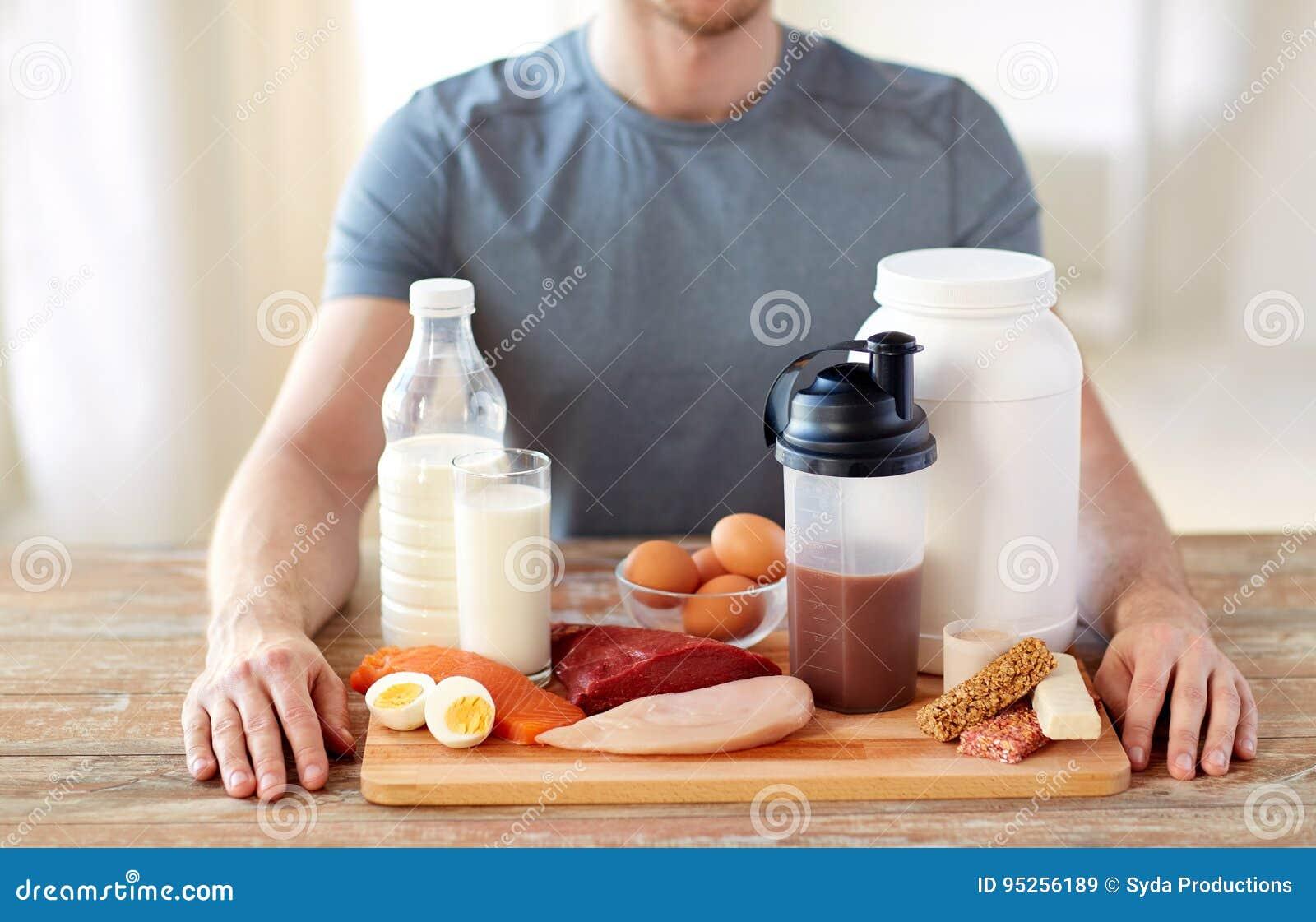 Ciérrese para arriba de hombre con ricos de la comida en proteína en la tabla