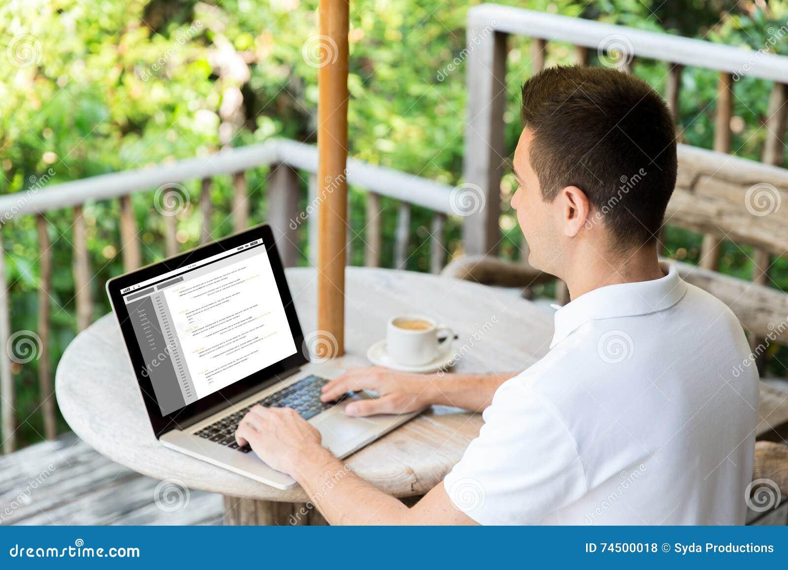 Ciérrese para arriba de hombre de negocios con el ordenador portátil en terraza