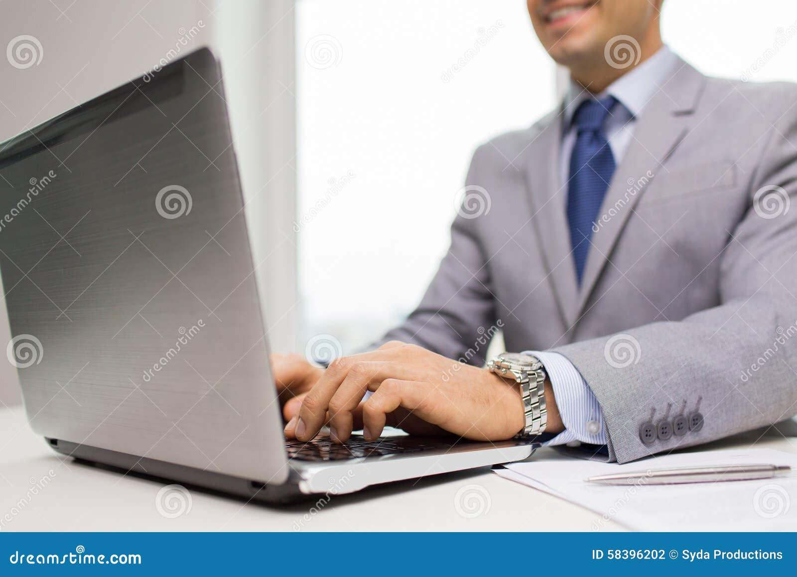 Ciérrese para arriba de hombre de negocios con el ordenador portátil y los papeles