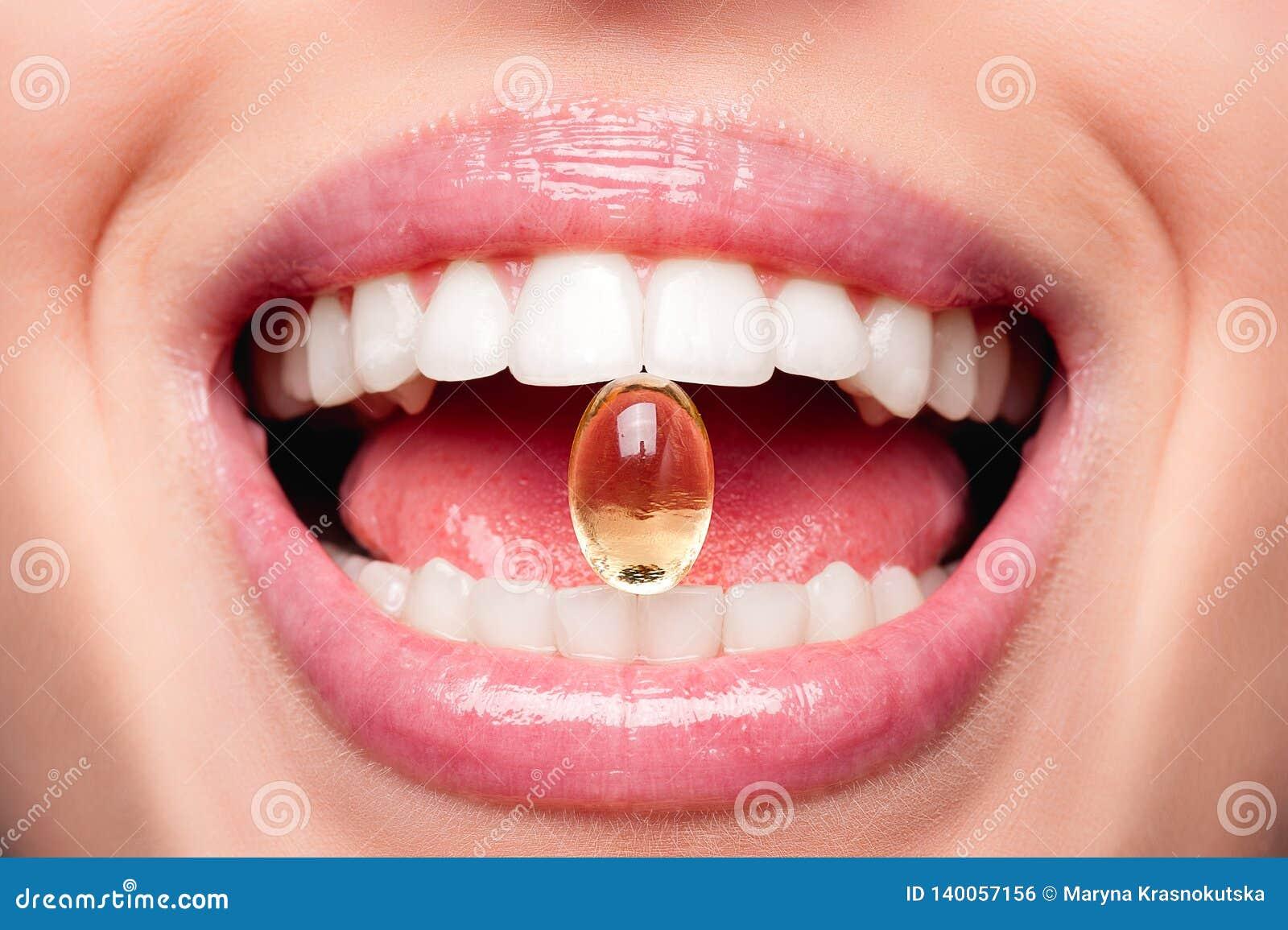 Ciérrese para arriba de la boca abierta mujer hermosa que sostiene la píldora del aceite de pescado en los dientes blancos Cápsul