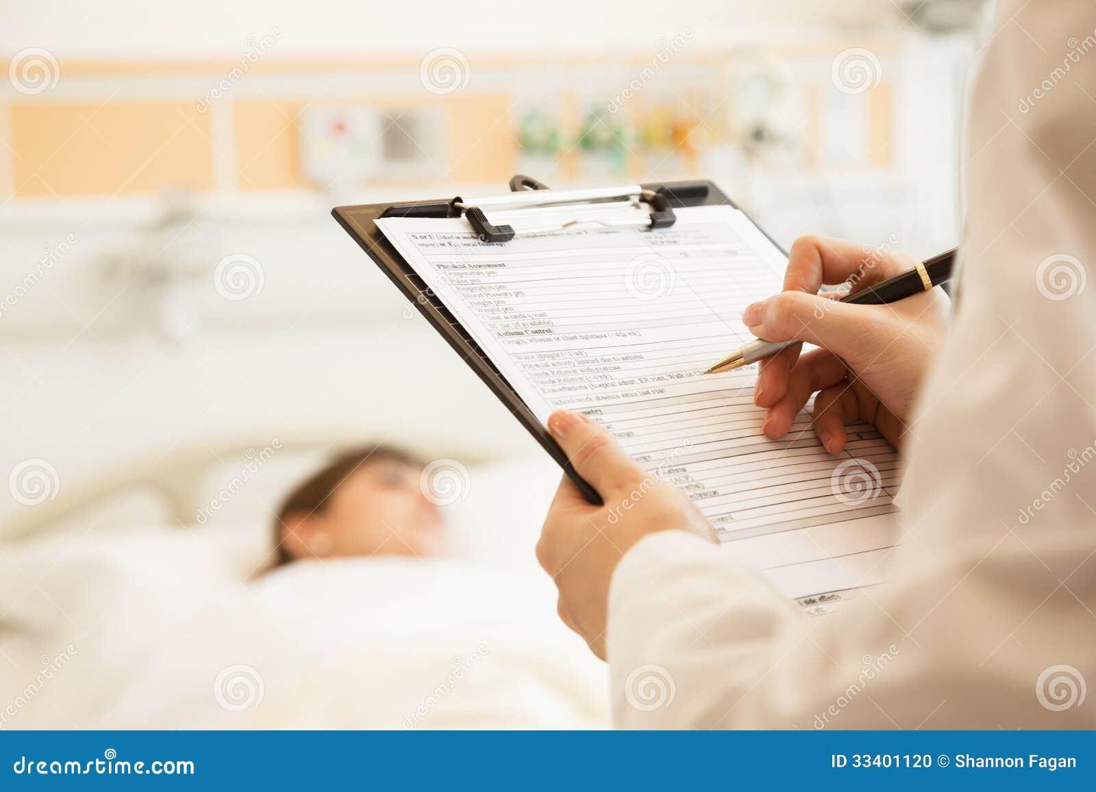 Ciérrese para arriba de la escritura del doctor en una carta médica con el paciente que miente en una cama de hospital en el fondo