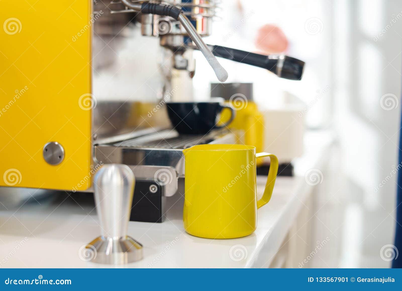Ciérrese para arriba de la máquina moderna del café y del pincher amarillo en contador de la barra