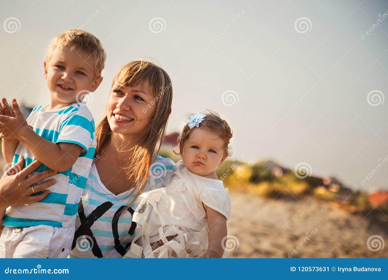 Ciérrese para arriba de la madre sonriente joven que abraza a sus pequeños niños, divirtiéndose en la playa juntos, concepto de f
