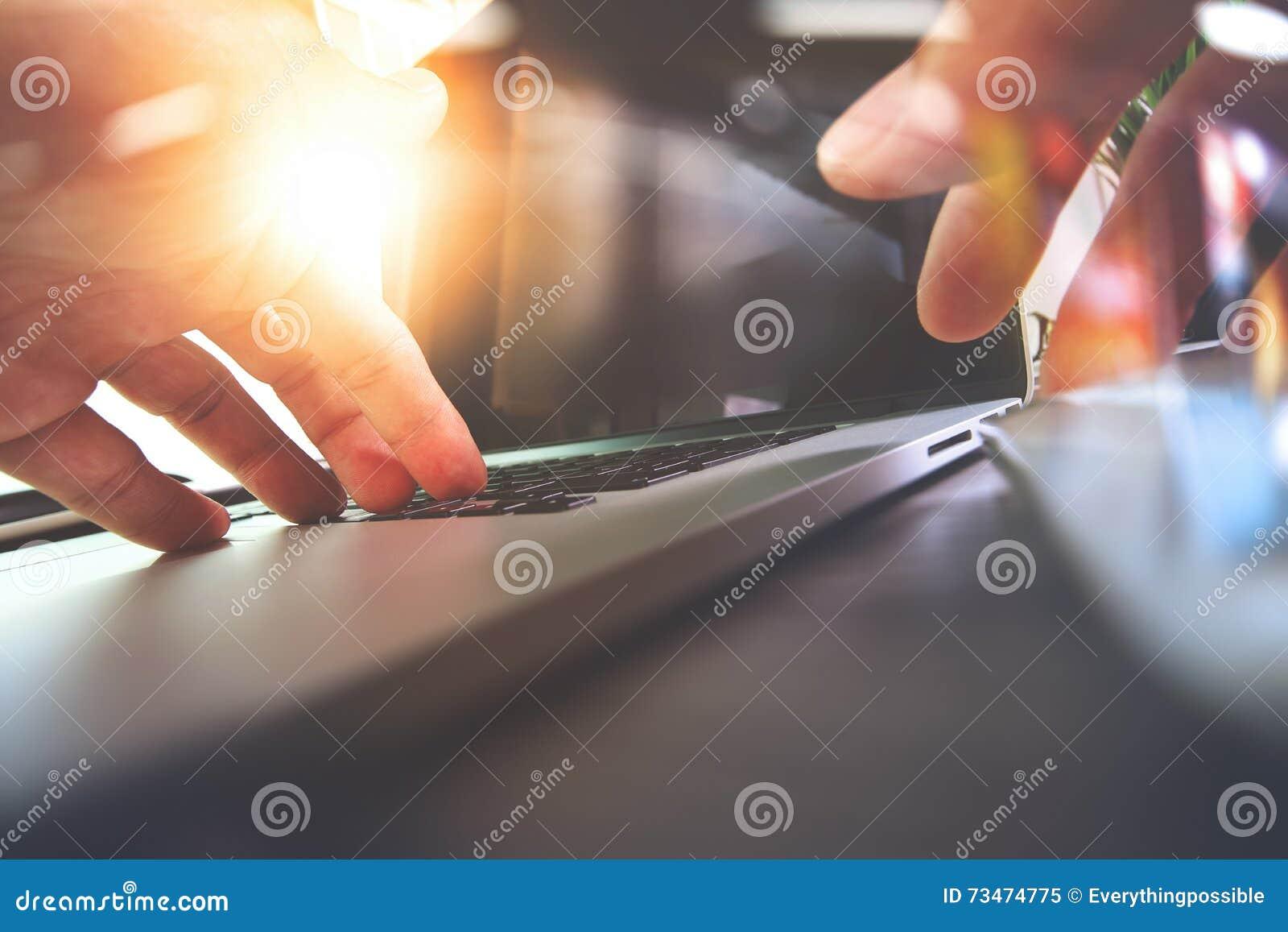 Ciérrese para arriba de la mano del diseñador que trabaja con el ordenador portátil en de madera