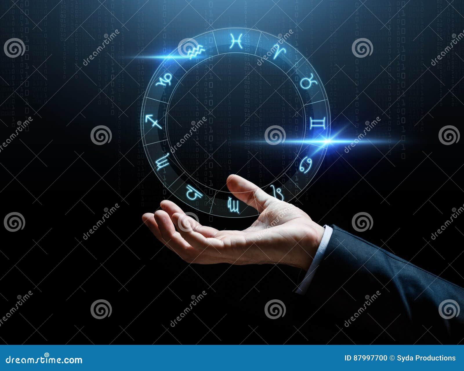 Ciérrese para arriba de la mano del hombre de negocios con las muestras del zodiaco