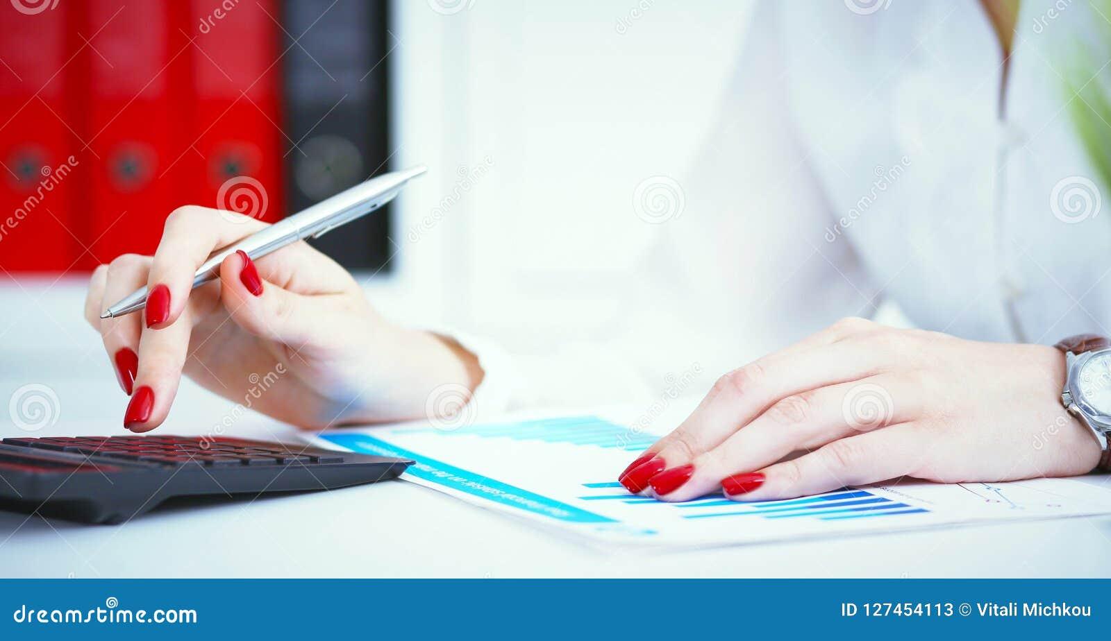 Ciérrese para arriba de la mano femenina del contable o del banquero que hace cálculos Ahorros, finanzas y concepto de la economí