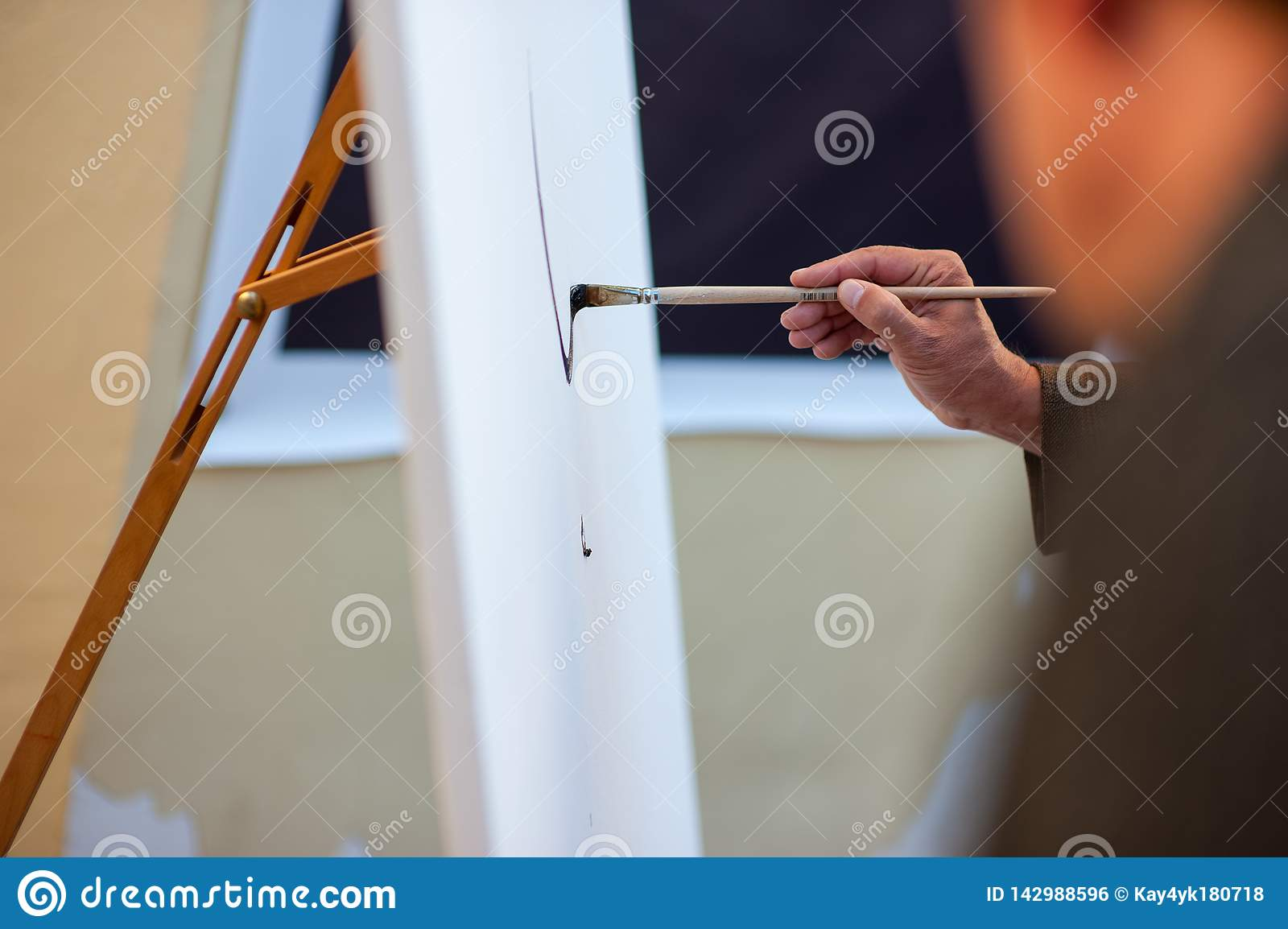 Ciérrese para arriba de la mano de la mujer del artista con la imagen de la pintura del cepillo en lona en el dibujo de la creati