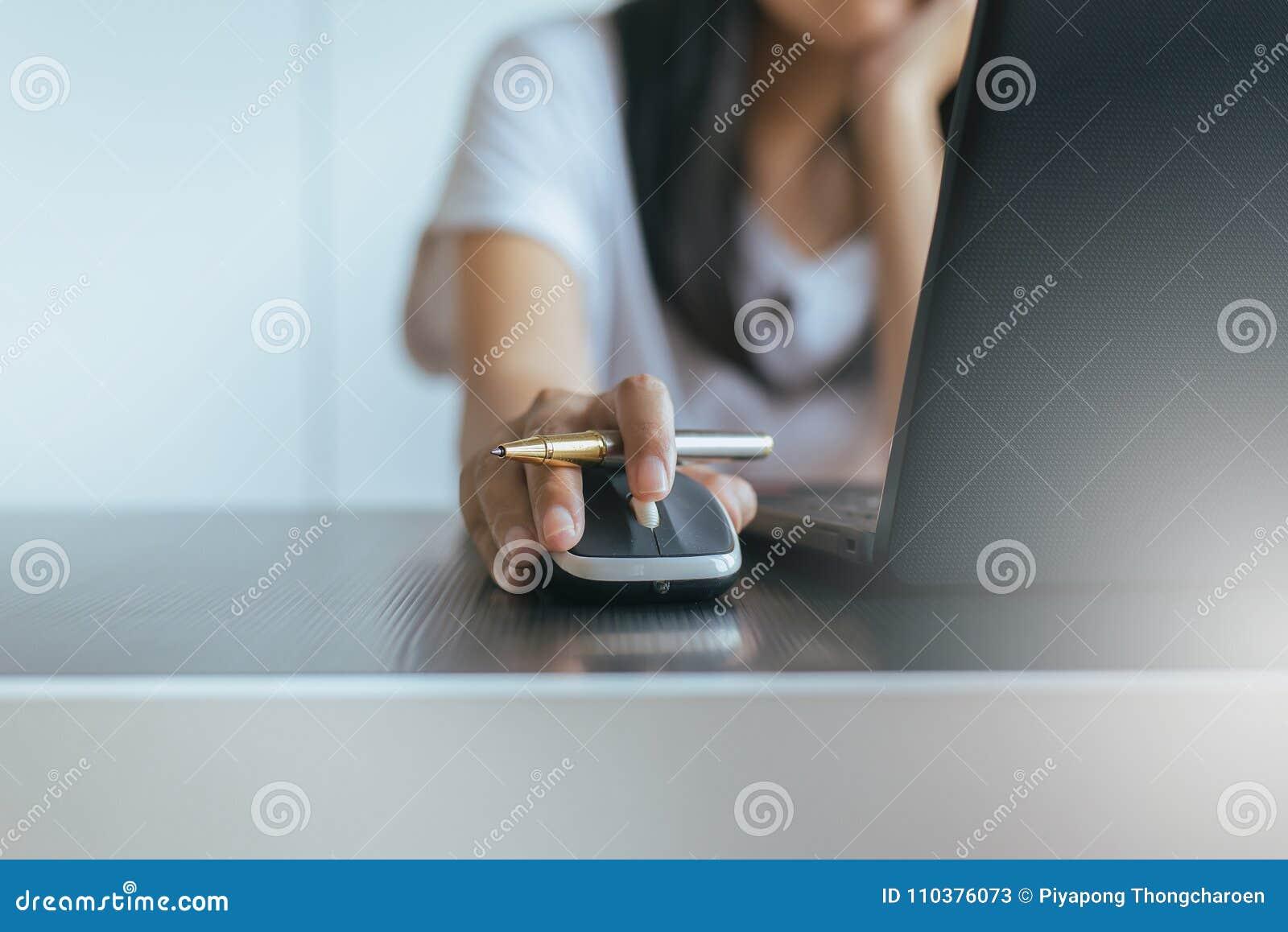 Ciérrese para arriba de la mujer de la mano serching y haga clic el ratón usando el ordenador portátil