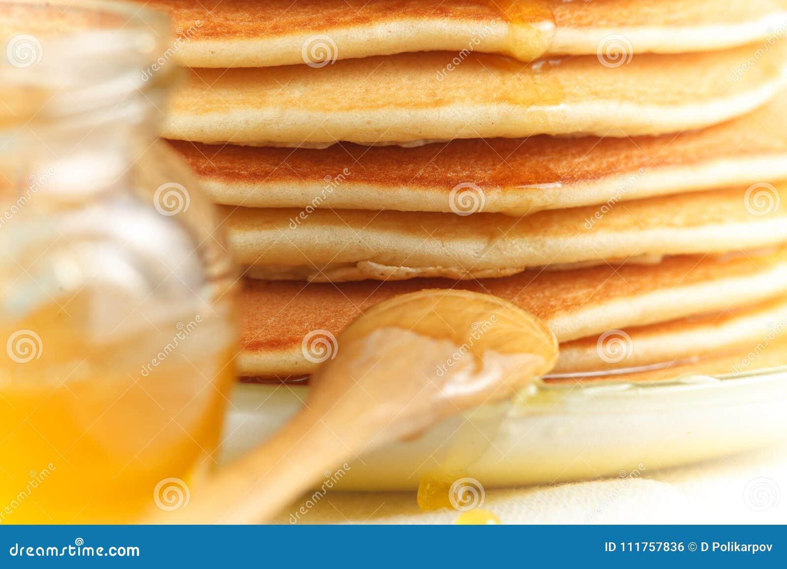 Ciérrese para arriba de la pila de crepe con la miel de colada, la cuchara de madera y el tarro de miel