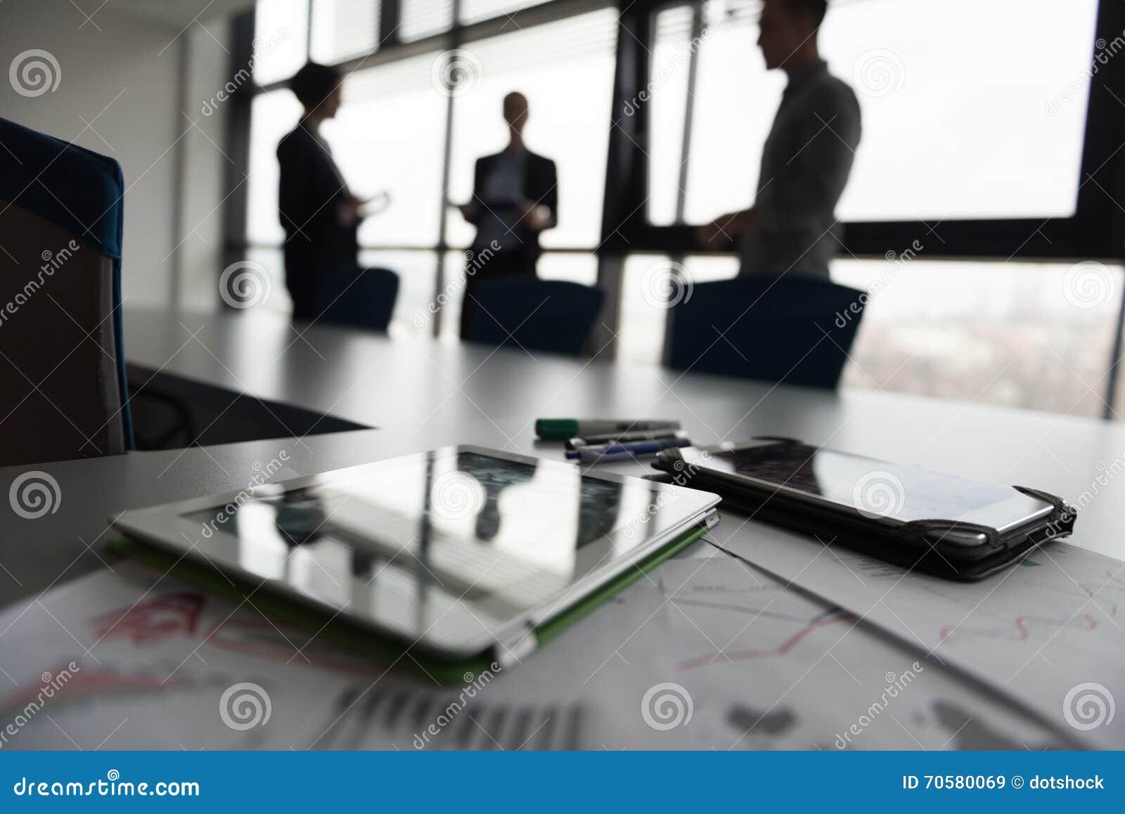Ciérrese para arriba de la tableta, hombres de negocios en la reunión en fondo