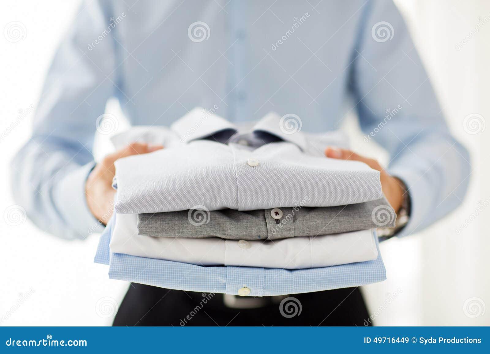 Ciérrese para arriba de las camisas dobladas tenencia del hombre de negocios