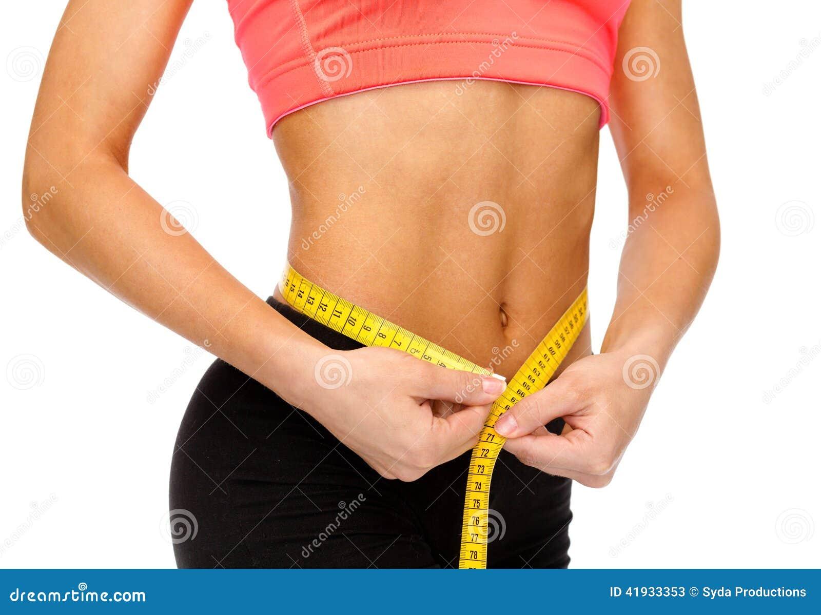Ciérrese para arriba de las manos femeninas que miden la cintura