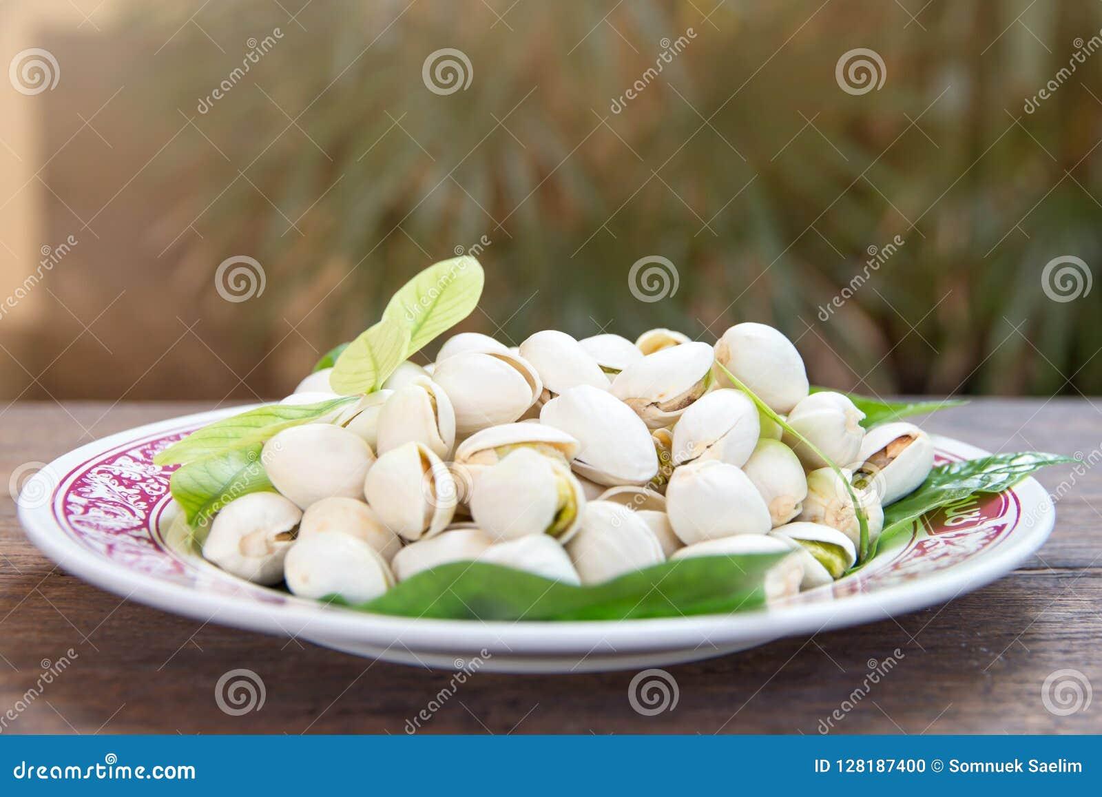 Ciérrese para arriba de las nueces de pistachos en la tabla de madera Pistacho en de madera