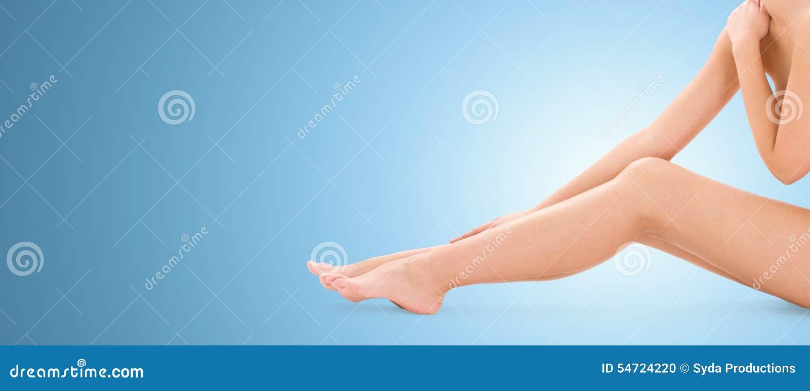 Ciérrese para arriba de las piernas desnudas de la mujer sobre fondo azul