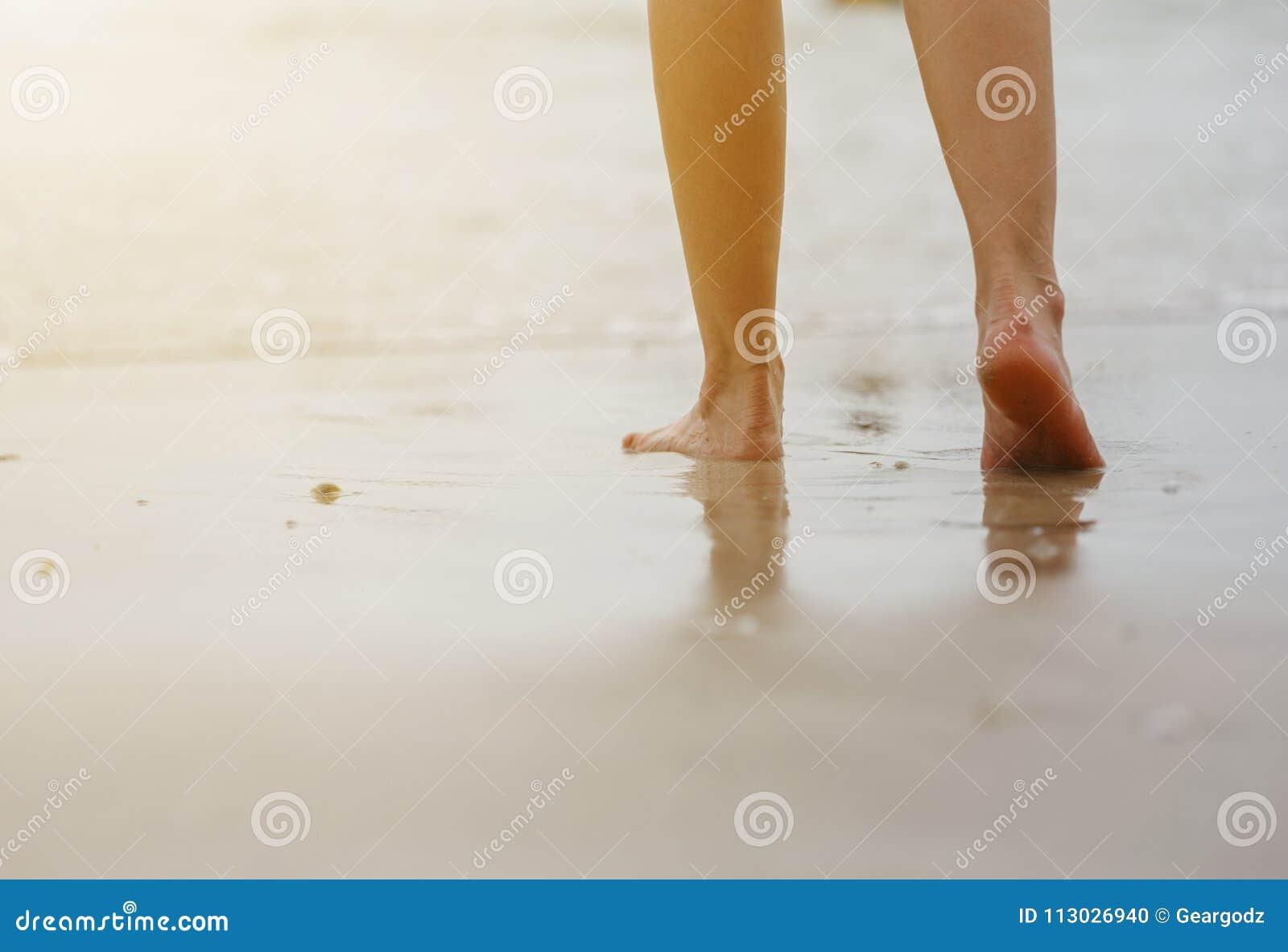 Ciérrese para arriba de las piernas femeninas que caminan en la playa