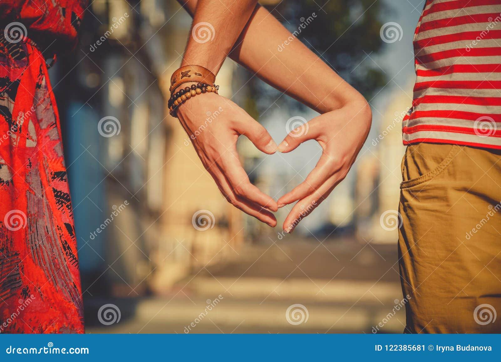 Ciérrese para arriba de los pares cariñosos que hacen forma del corazón con las manos en la calle de la ciudad verano