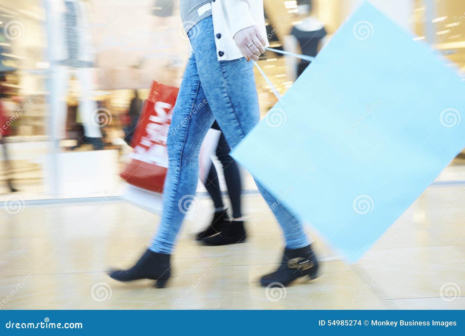 Ciérrese para arriba de los pies de los compradores que llevan bolsos en alameda de compras