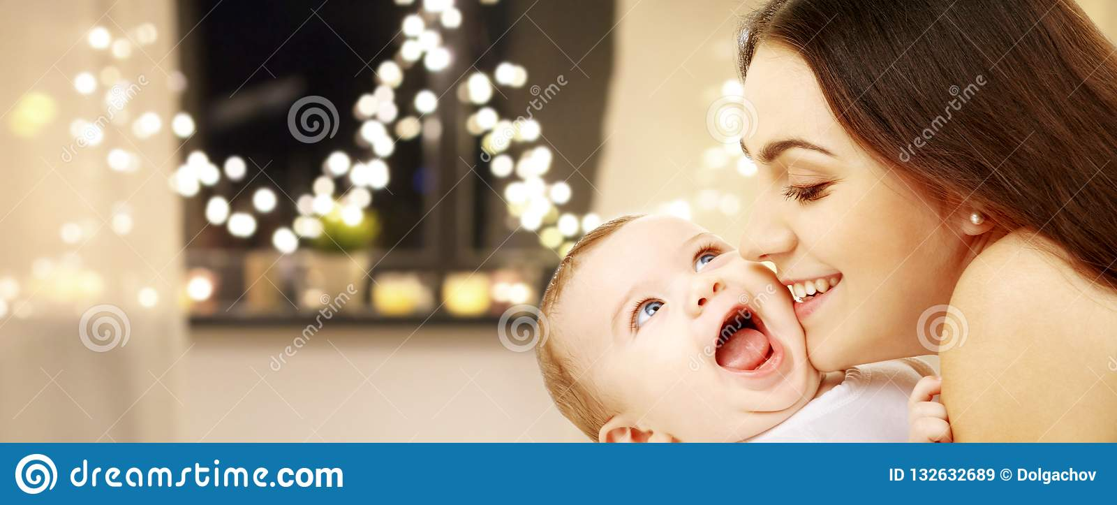 Ciérrese para arriba de madre con el bebé sobre luces de la Navidad