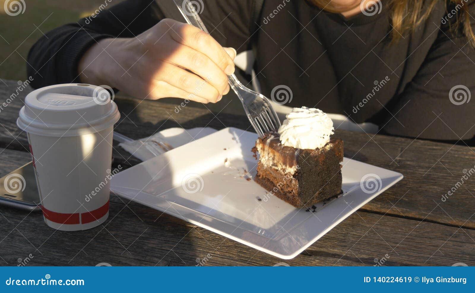 Ciérrese para arriba de mujer para tomar un pedazo de torta con la bifurcación