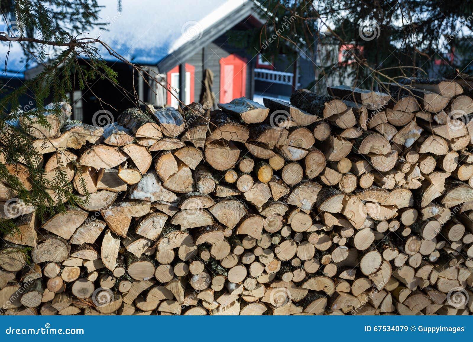 Ciérrese para arriba de pila de madera recientemente tajada con una cabina en el backgr