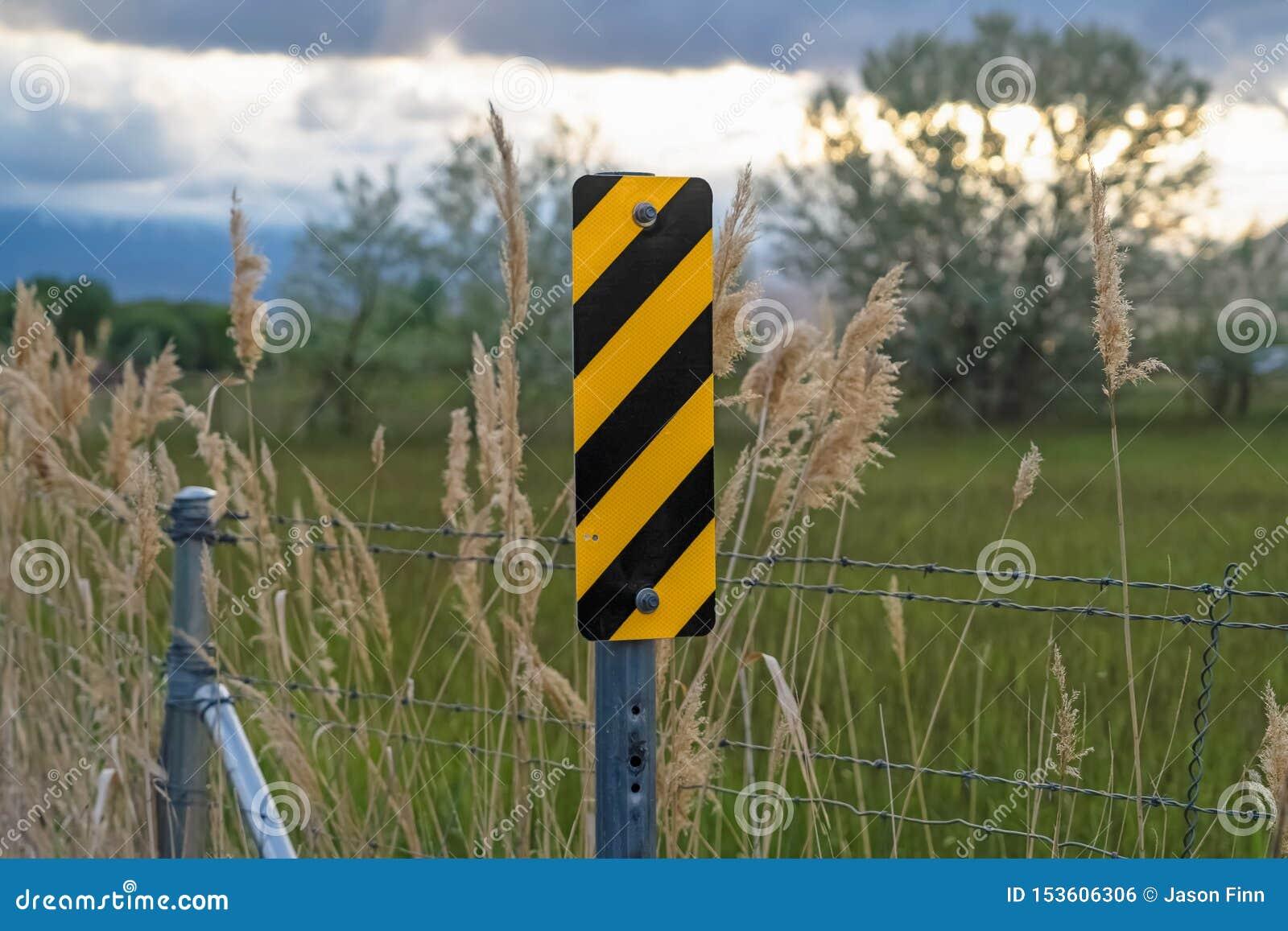 Ciérrese para arriba de señal de tráfico diagonal negra y amarilla de las rayas al lado de la cerca del alambre de púas
