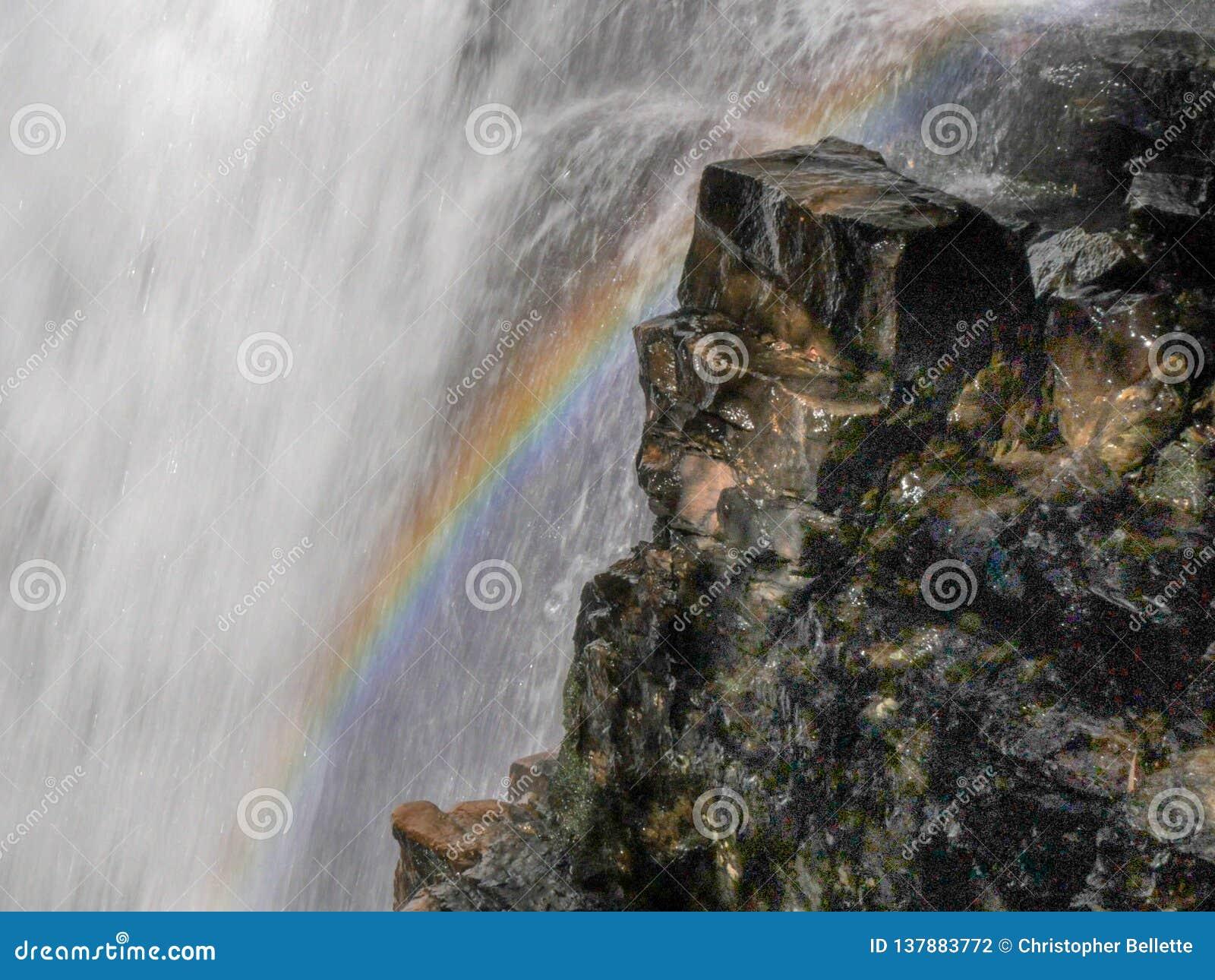 Ciérrese para arriba de un arco iris al borde de las caídas de ferguson en la pista terrestre popular de Tasmania