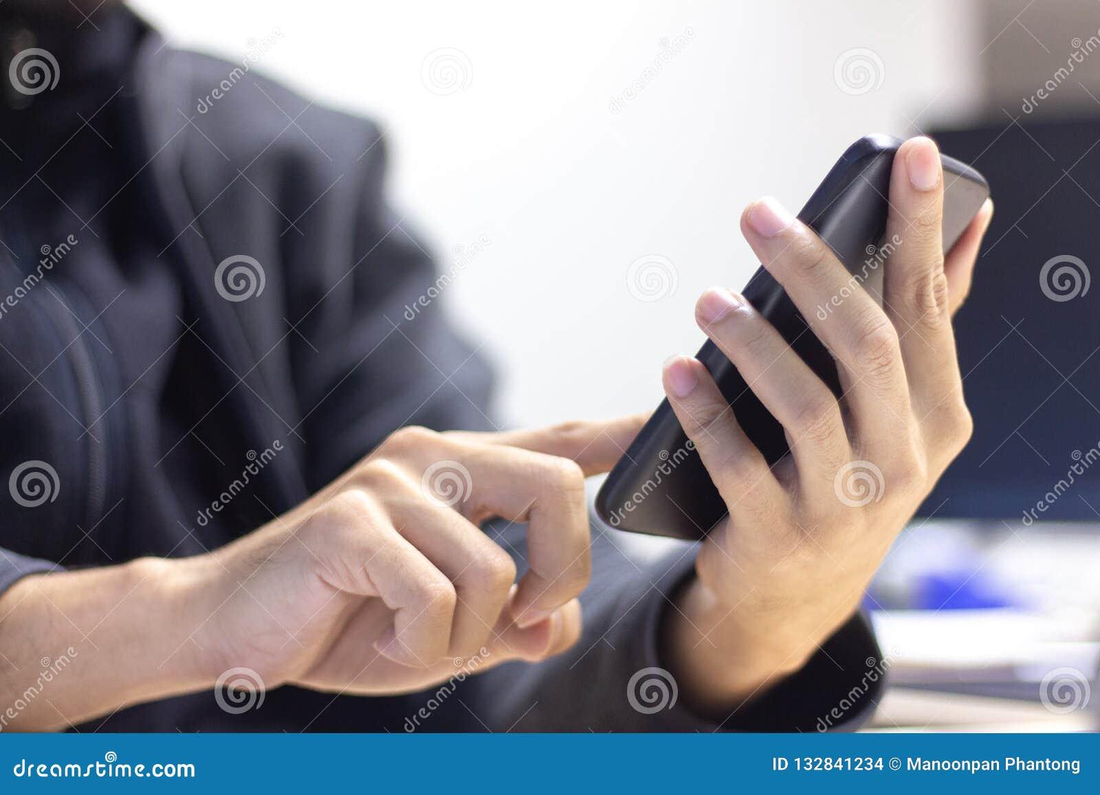 Ciérrese para arriba de un hombre que usa el teléfono elegante móvil