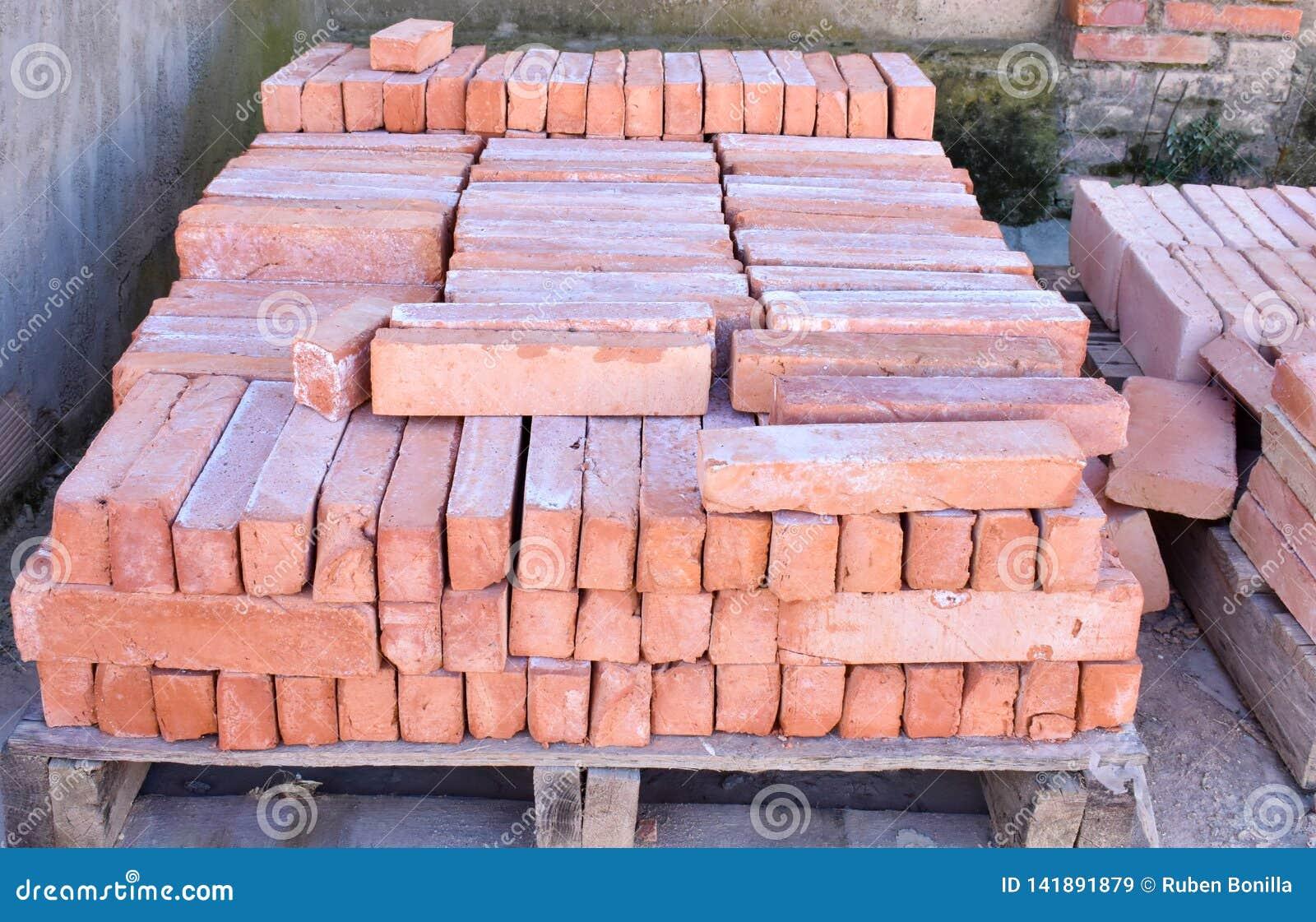 Ciérrese para arriba de un un montón de madera de la plataforma de ladrillos rojos apilados viejos Los ladrillos se piden en much