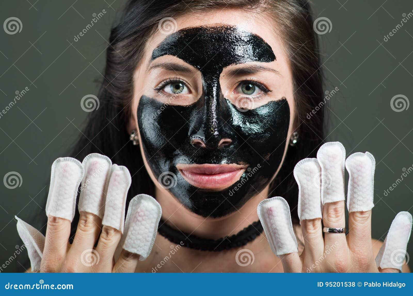 Ciérrese para arriba de una mujer joven de la belleza que usa una mascarilla negra y llevando el protector de los clavos en sus c